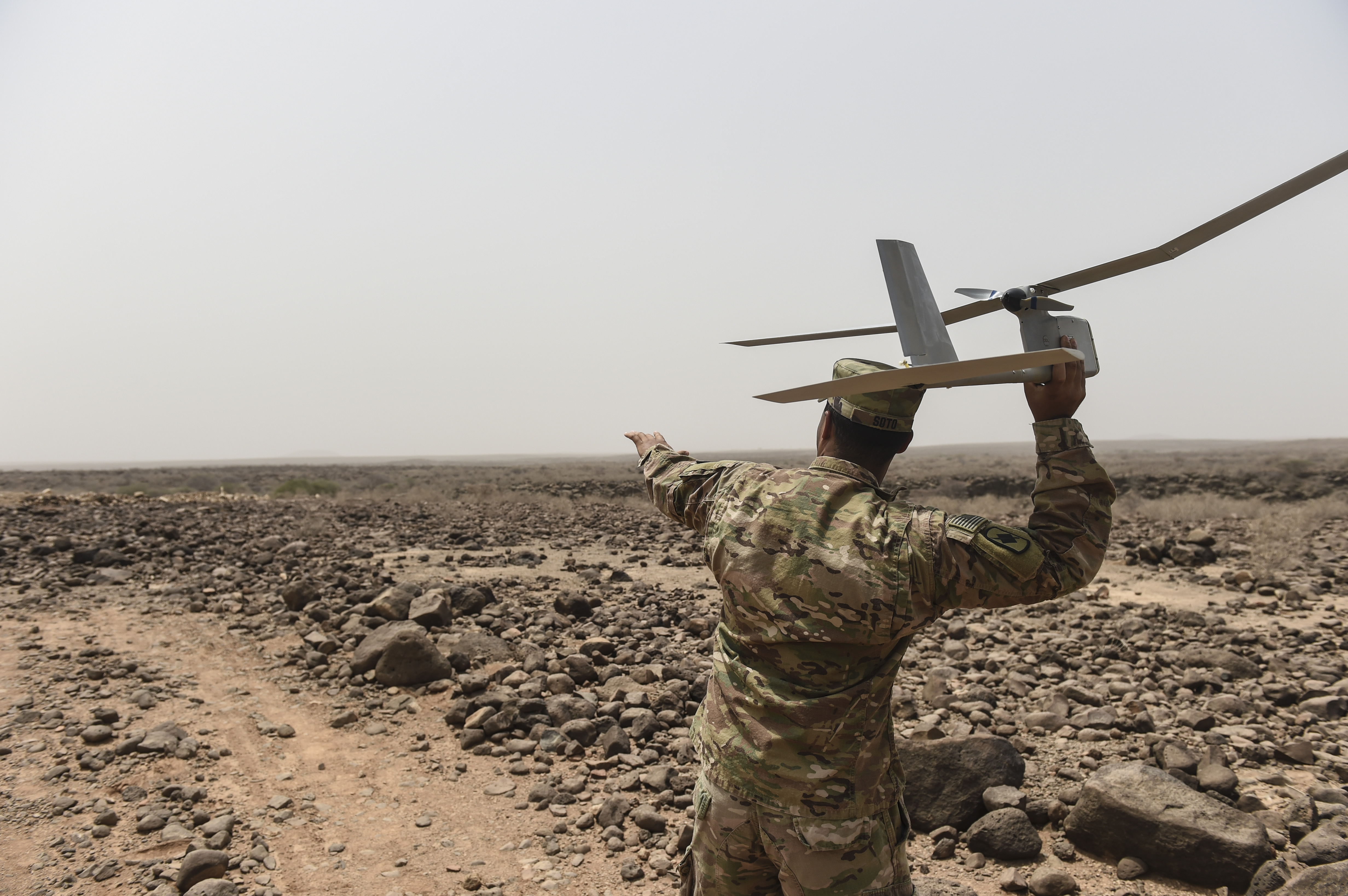 U.S. Army Spc. Enrique Soto, assigned to the 1st Battalion, 153rd Infantry Regiment, Task Force Warrior, an associated unit of Combined Joint Task Force - Horn of Africa, demonstrates a hand launch of a RQ-11 Raven remotely piloted aircraft in an airfield in southern Djibouti, Aug. 21, 2017. The demonstration was an effort to familiarize Djibouti Armed Forces members with the unmanned aerial vehicle system, clear up confusion about the Raven and other RPAs, and show the safe operation of the Raven. (U.S. Air Force photo by Staff Sgt. Eboni Prince)