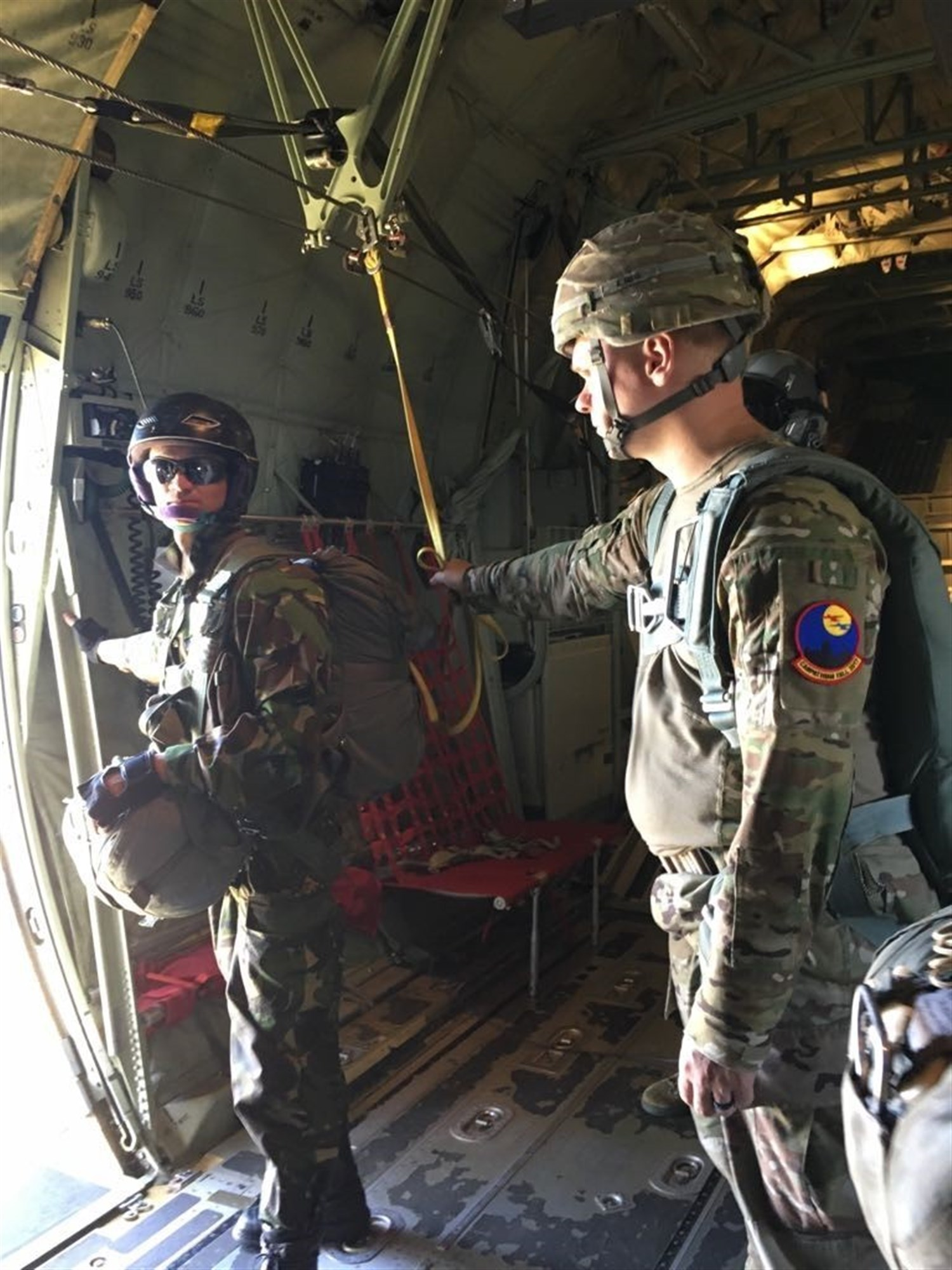 Sgt. Nicholas August performs safety duties as a jumpmaster for Romanian paratroopers while the Romanian jumpmaster checks the aircraft door to ensure the exit is safe. Twelve paratroopers 16th Special Troops Battalion conducted airborne operations alongside more than 220 Romanian paratroopers and jumpmasters.