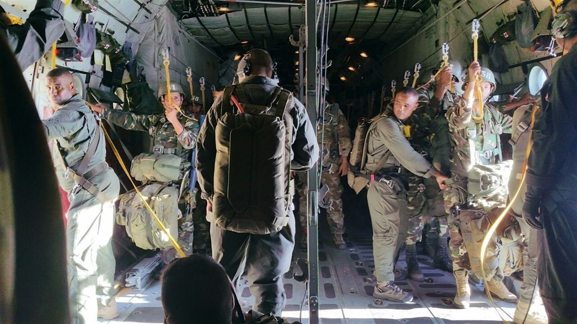 Tunisian paratroopers and jumpmasters ensure the safety of every paratrooper before conducting jumps from a C-130J aircraft. The 37 Tunisian paratroopers, equipped with T-10 parachutes, were aboard the aircraft along with 12 paratroopers from the 16th Special Troops Battalion.