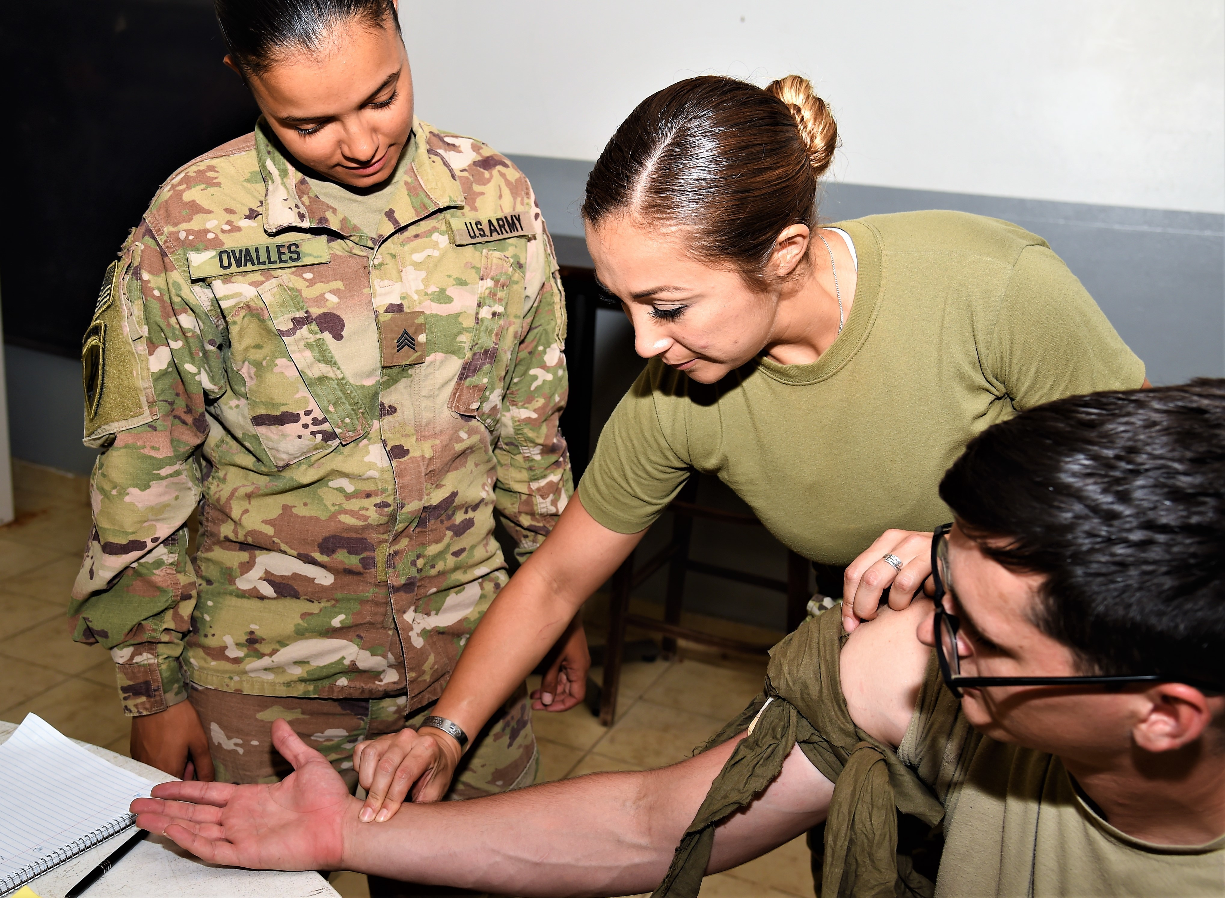 U.S. Army Staff Sgt, Crystal Velasquez, Combined Joint Task Force-Horn of Africa senior enlisted medical advisor and course instructor, instructs U.S. Army Sgt. Marina Ovalles, CJTF-HOA supply sergeant, and U.S. Air Force Staff Sgt. Christopher Faucette, Combined Joint Task Force-Horn of Africa transportation motor pool, on applying a combat application tourniquet during combat lifesaver course held on Camp Lemonnier, Djibouti, Sept. 11, 2017. The U.S. Army Combat Lifesaver Course is intended to bridge first aid training – self and buddy care — and the medical training given to combat medics. (U.S. Air National Guard photo by Tech. Sgt. Andria Allmond)