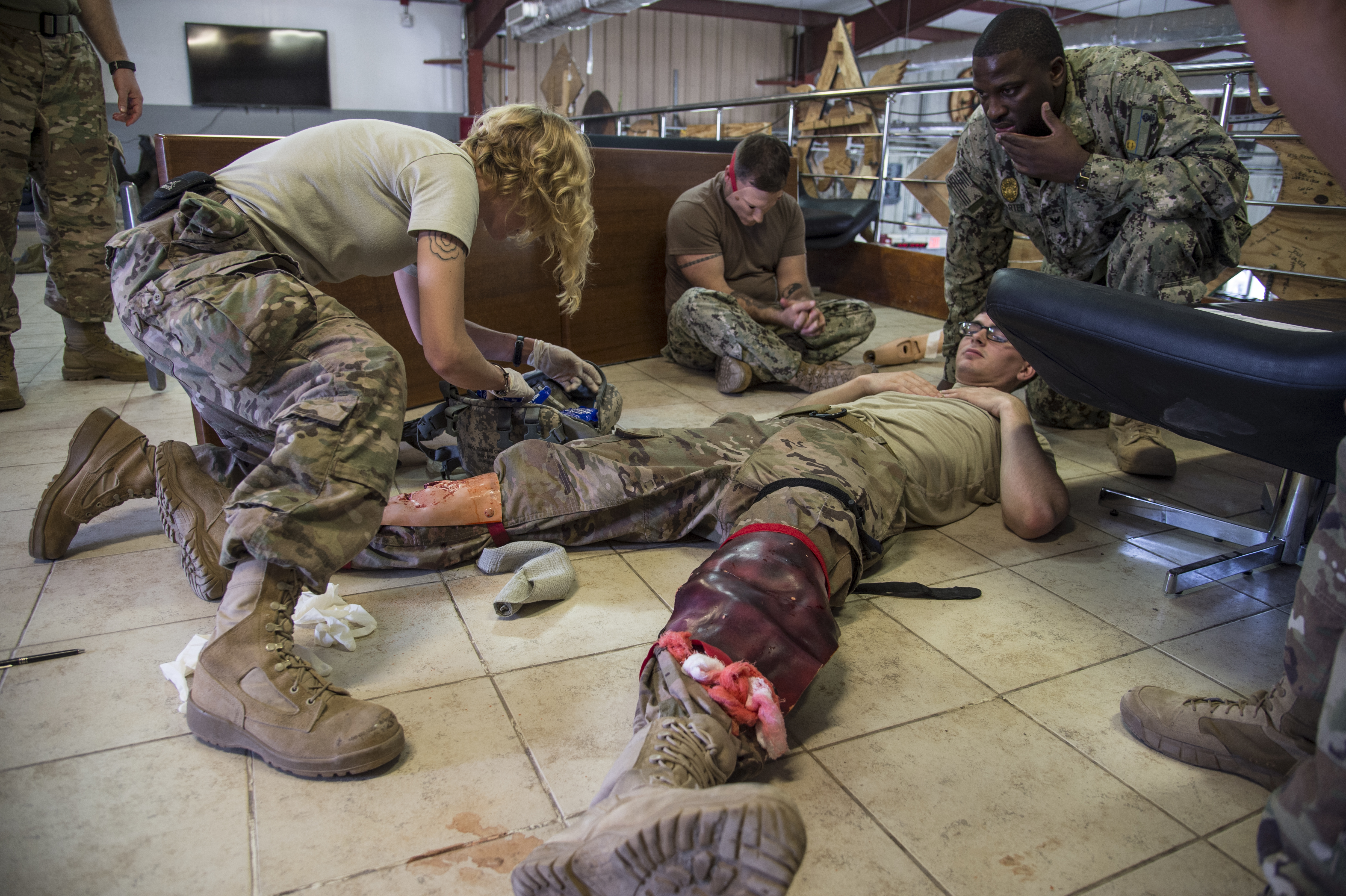 U.S. Air Force Tech. Sgt. Andria Allmond, Combined Joint Task Force-Horn of Africa, treats mock casualties during the tactical field care part of the combat lifesaver course practical assessment held on Camp Lemonnier, Djibouti, Sept. 14, 2017. The five-day course consists of 40 hours of blended classroom and hands-on training given by certified combat medics. The Army medics open the course to all military branches here. (U.S. Air National Guard photo by Tech. Sgt. Joe Harwood)