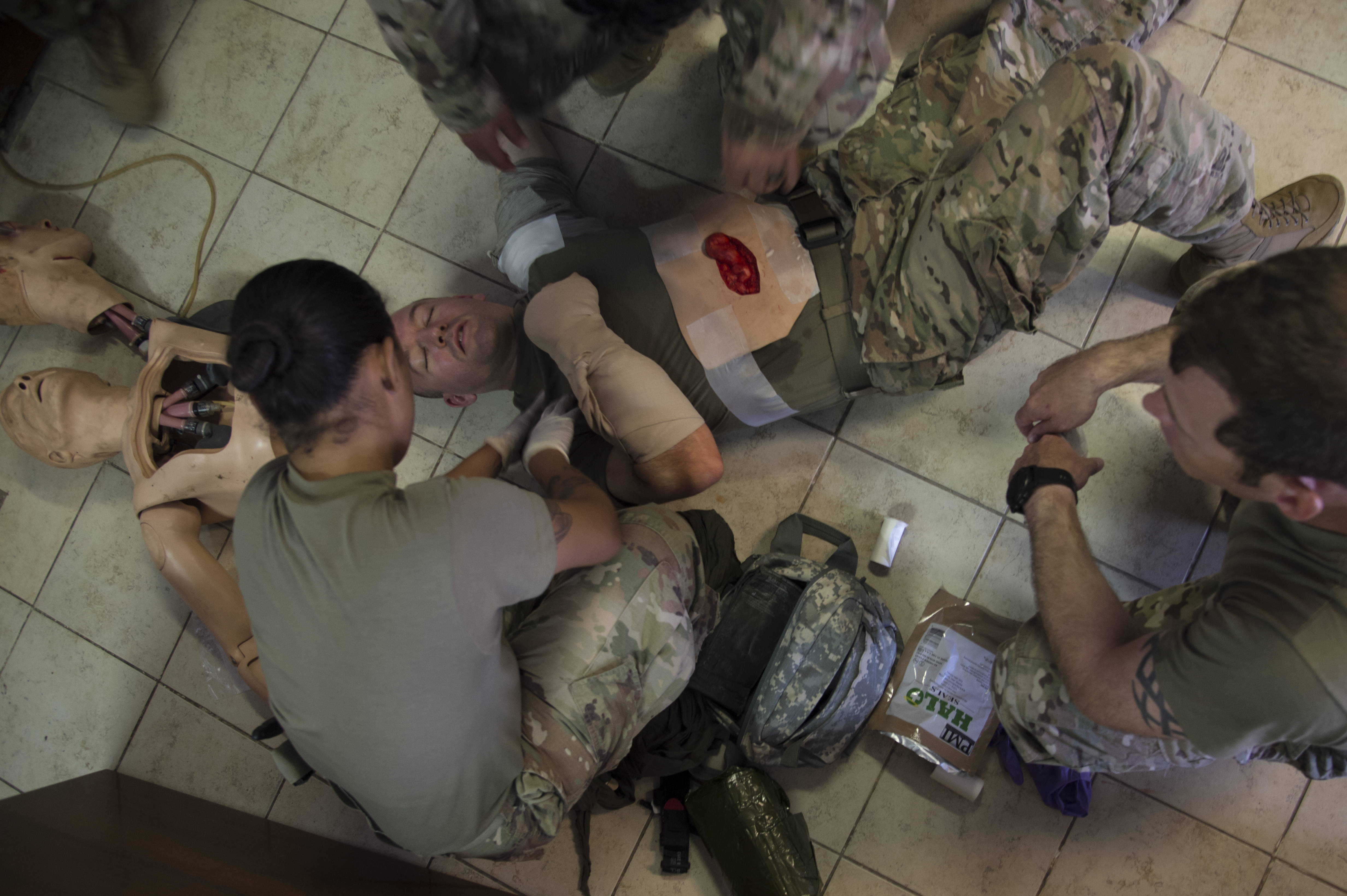 U.S. Army Sgt. Marina Ovalles, Combined Joint Task Force-Horn of Africa supply sergeant, treats multiple simulated wounds during the practical application assessment portion of the test to certify in the combat lifesaver course held on Camp Lemonnier, Djibouti, Sept. 15, 2017. The U.S. Army Combat Lifesaver Course is intended to bridge first aid training – self and buddy care — and the medical training given to combat medics. (U.S. Air National Guard photo by Tech. Sgt. Joe Harwood)