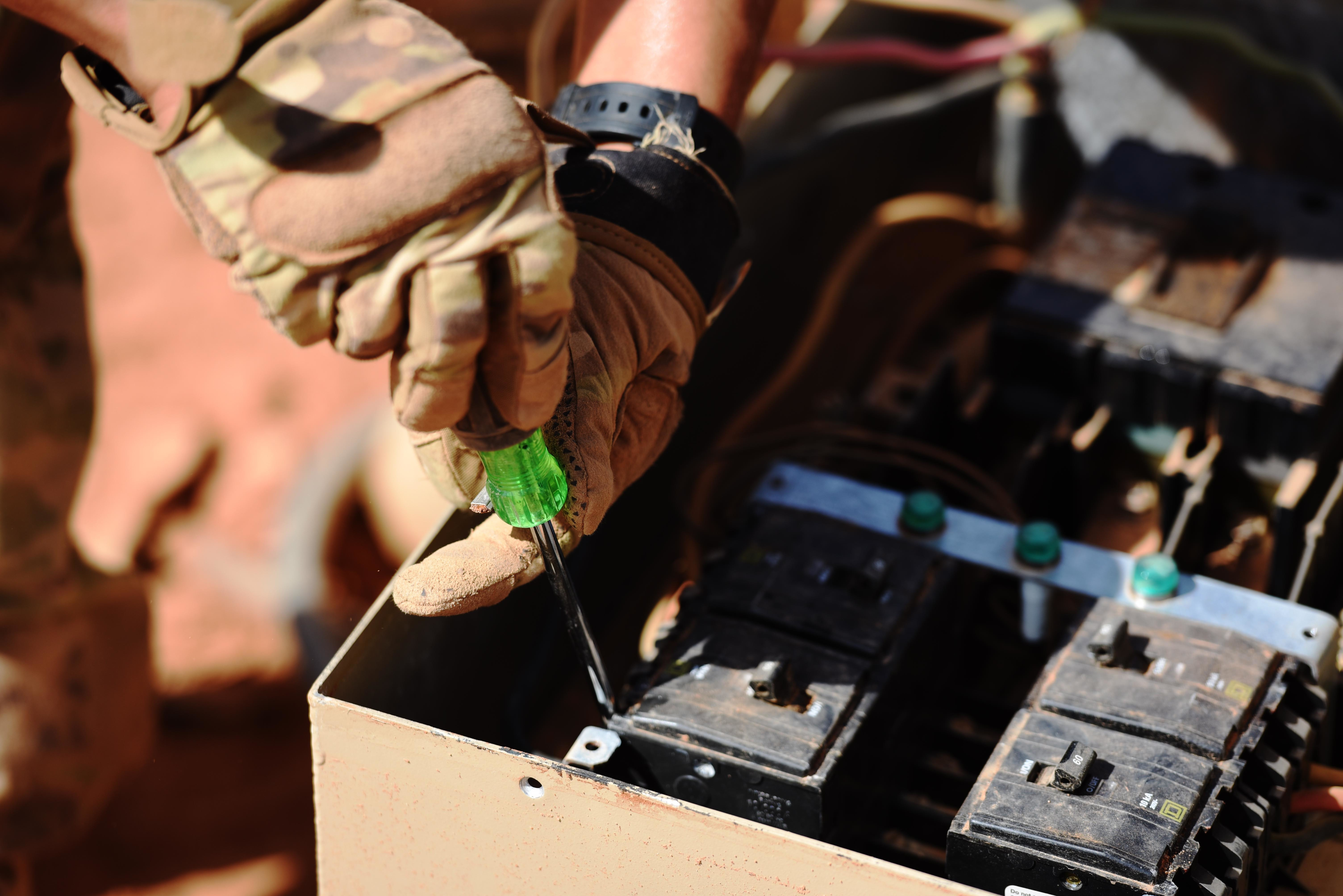 "An Airman from the 724th Expeditionary Air Base Squadron works on electric equipment connected to cold storage units at a new base location, Sept. 09, 2017, at Air Base 201, Agadez, Niger. The move to the bigger base is called ""FLEXIT,"" short for ""Flintlock Exit."" All the electrical equipment at Air Base 201 must be able to function in hot weather and frequent dust storms. (U.S. Air Force photo by Staff Sgt. Joshua R. M. Dewberry/released)"