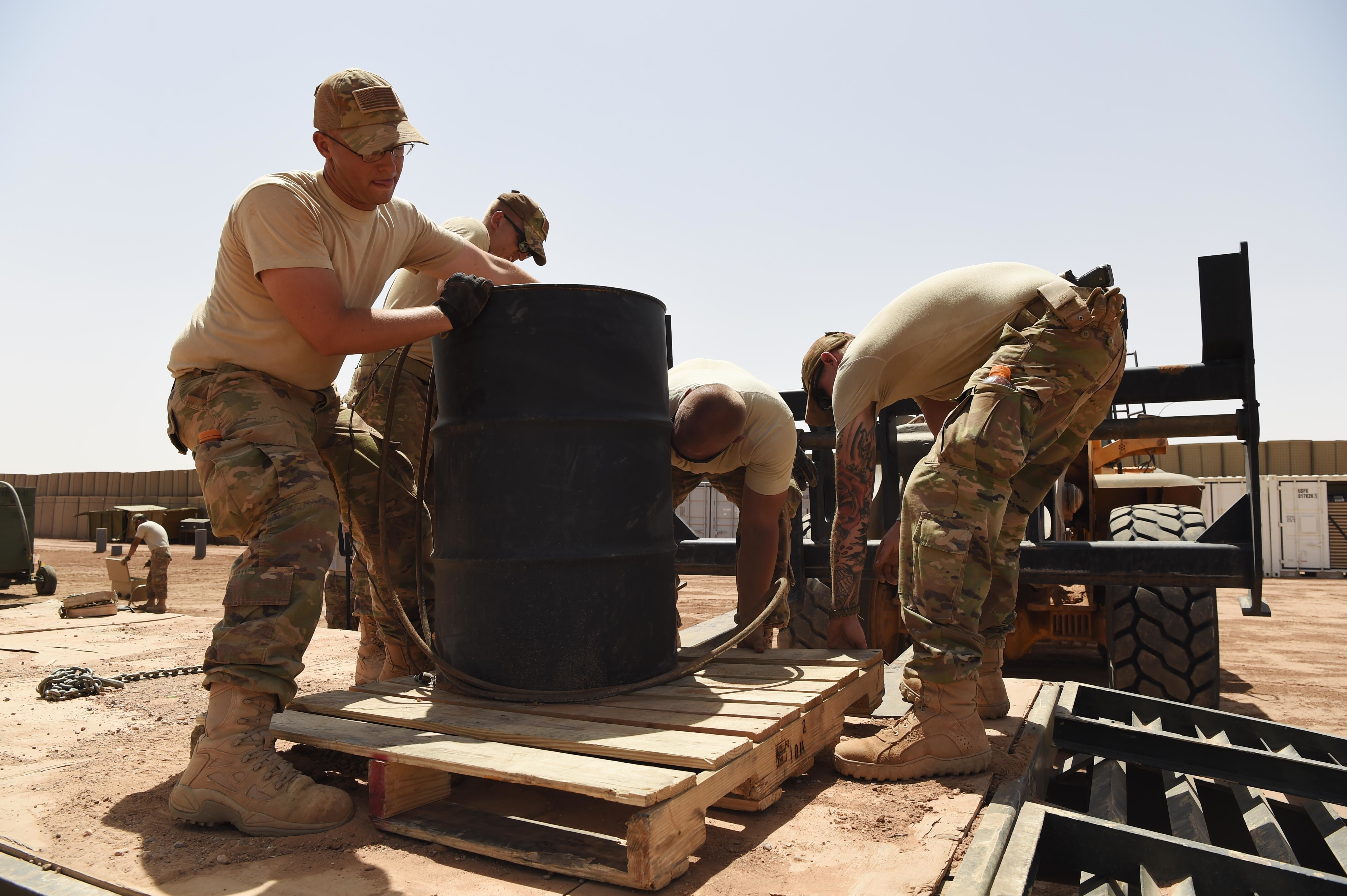 "Airmen from the 724th Expeditionary Air Base Squadron move barrels of gas from their old camp site to a new location, Sept. 09, 2017, at Air Base 201, Agadez, Niger. The move to the bigger base is called ""FLEXIT,"" short for ""Flintlock Exit."" The fuel is used to power generators, in turn powering cold storage units, HVAC and general electric requirements. (U.S. Air Force photo by Staff Sgt. Joshua R. M. Dewberry/released)"