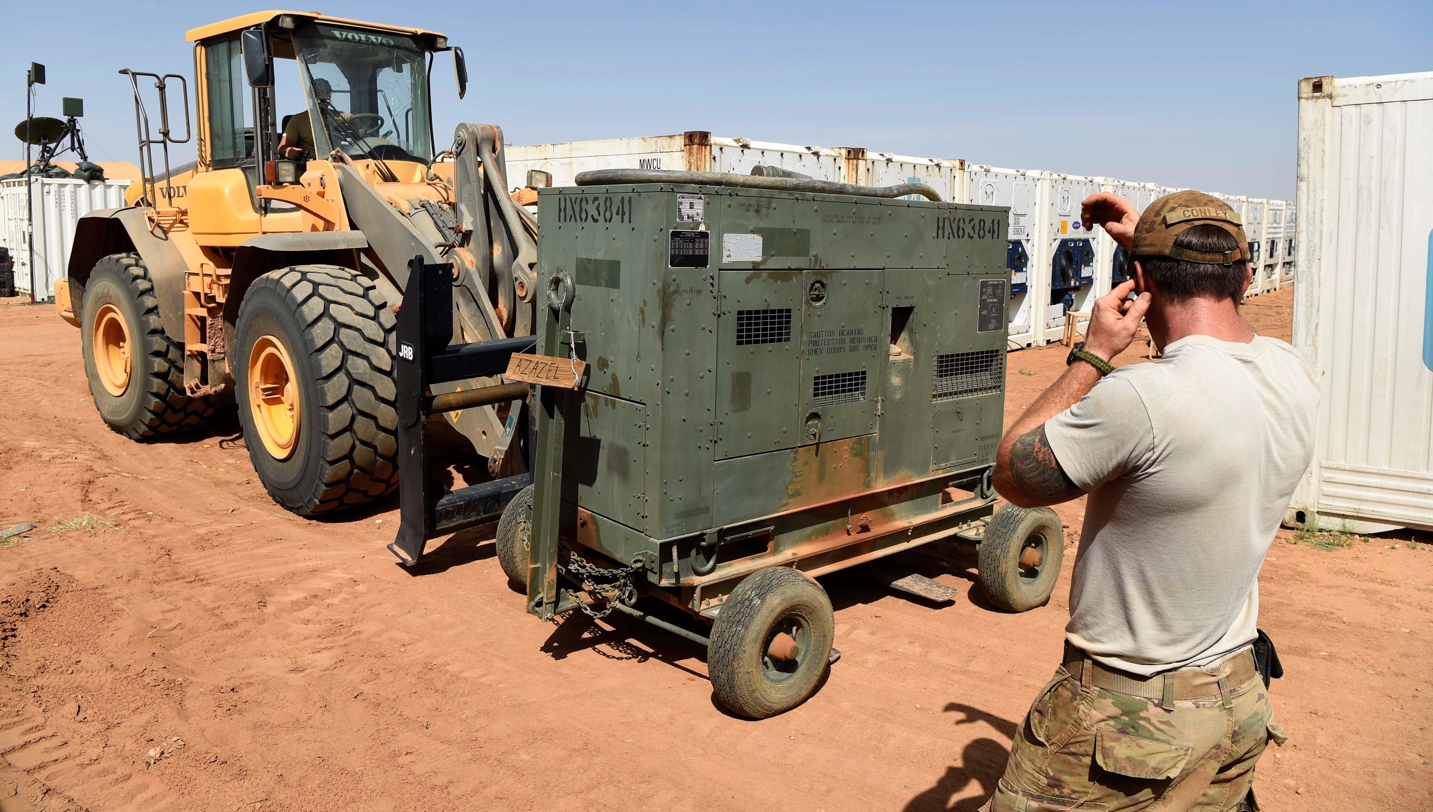 "Airmen from the 724th Expeditionary Air Base Squadron move generators from their old base to a new location, Sept. 09, 2017, at Air Base 201, Agadez, Niger. The move to the bigger base is called ""FLEXIT,"" short for ""Flintlock Exit."" Independent power sources are required to operate in such a remote location. (U.S. Air Force photo by Staff Sgt. Joshua R. M. Dewberry/released)"