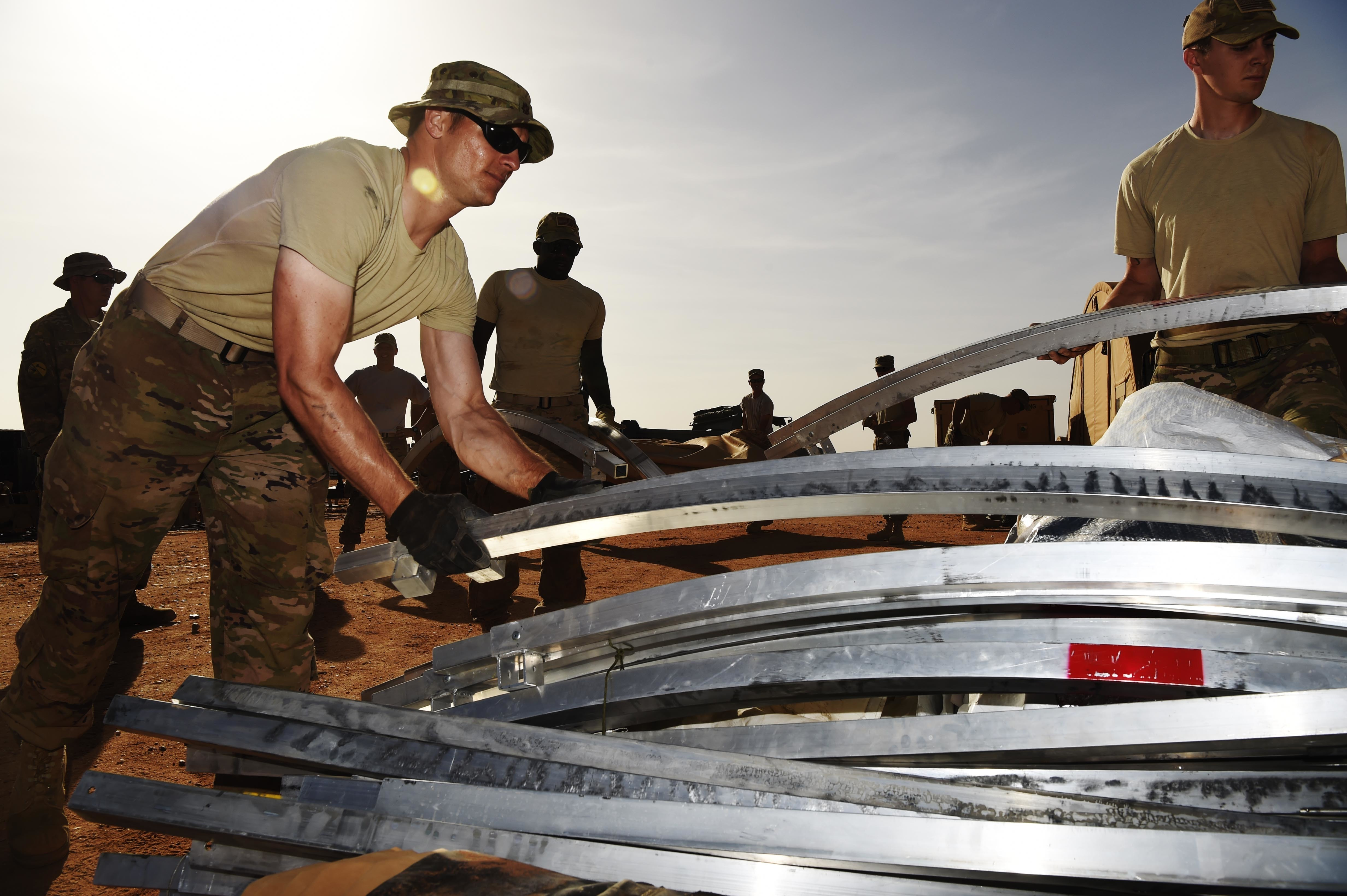 "Major Carsten Stahr (left), 724th Expeditionary Air Base Squadron director of operations, takes down tents from the old base to move to a new location, Sept. 11, 2017, at Air Base 201, Agadez, Niger. The move to the bigger base is called ""FLEXIT,"" short for ""Flintlock Exit."" Being located in this deployed environment requires tents to function as temporary housing in lieu of traditional infrastructure. (U.S. Air Force photo by Staff Sgt. Joshua R. M. Dewberry/released)"