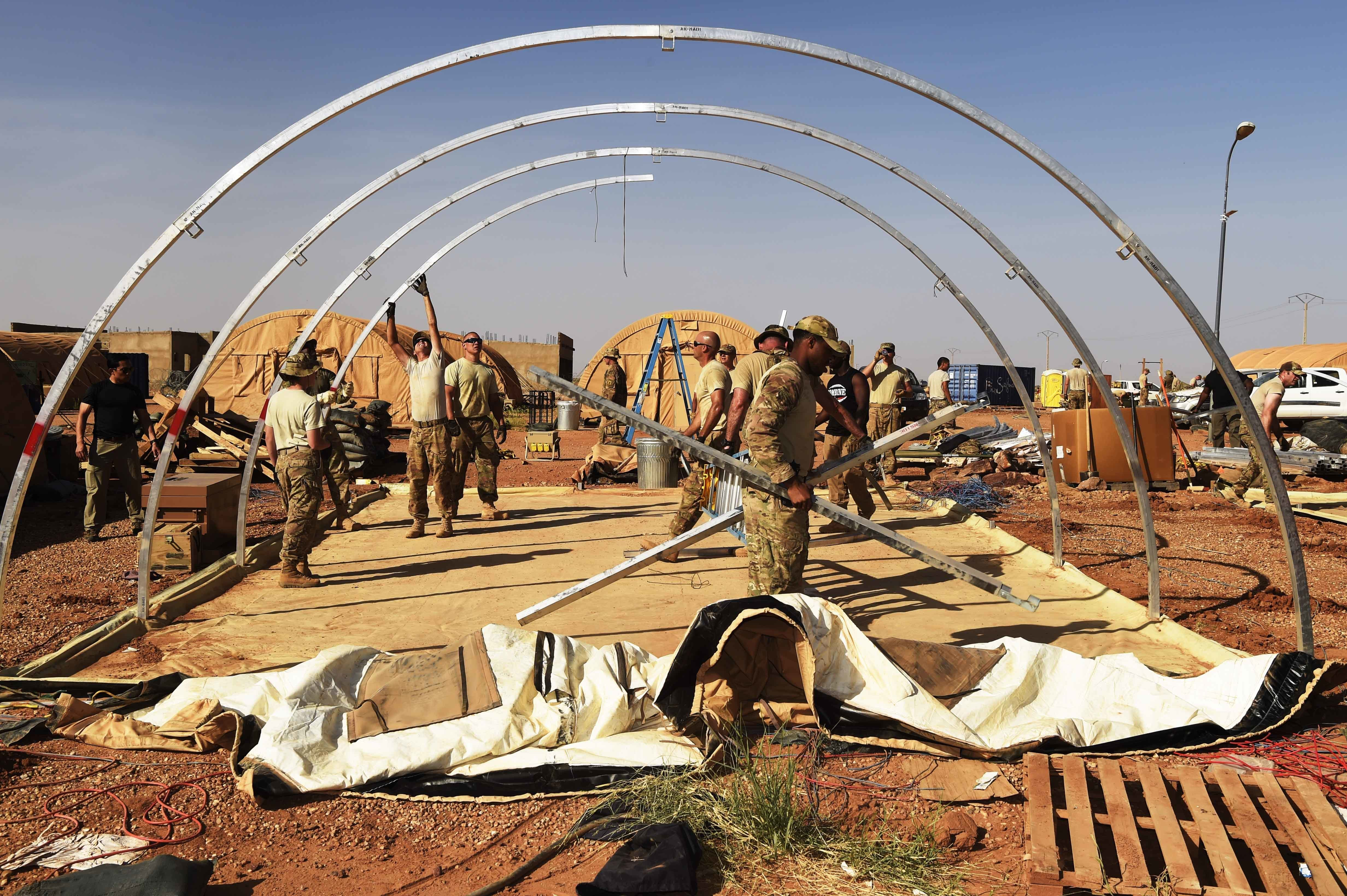 "Airmen from the 724th Expeditionary Air Base Squadron and Soldiers from the 411th Military Police Company, 89th MP Brigade, 1st Platoon, take down tents from the old base to move to a new location, Sept. 11, 2017,at Air Base 201, Agadez, Niger. The move to the bigger base is called ""FLEXIT,"" short for ""Flintlock Exit."" Being located in this deployed environment requires temporary housing in lieu of traditional infrastructure. (U.S. Air Force photo by Staff Sgt. Joshua R. M. Dewberry/released)"