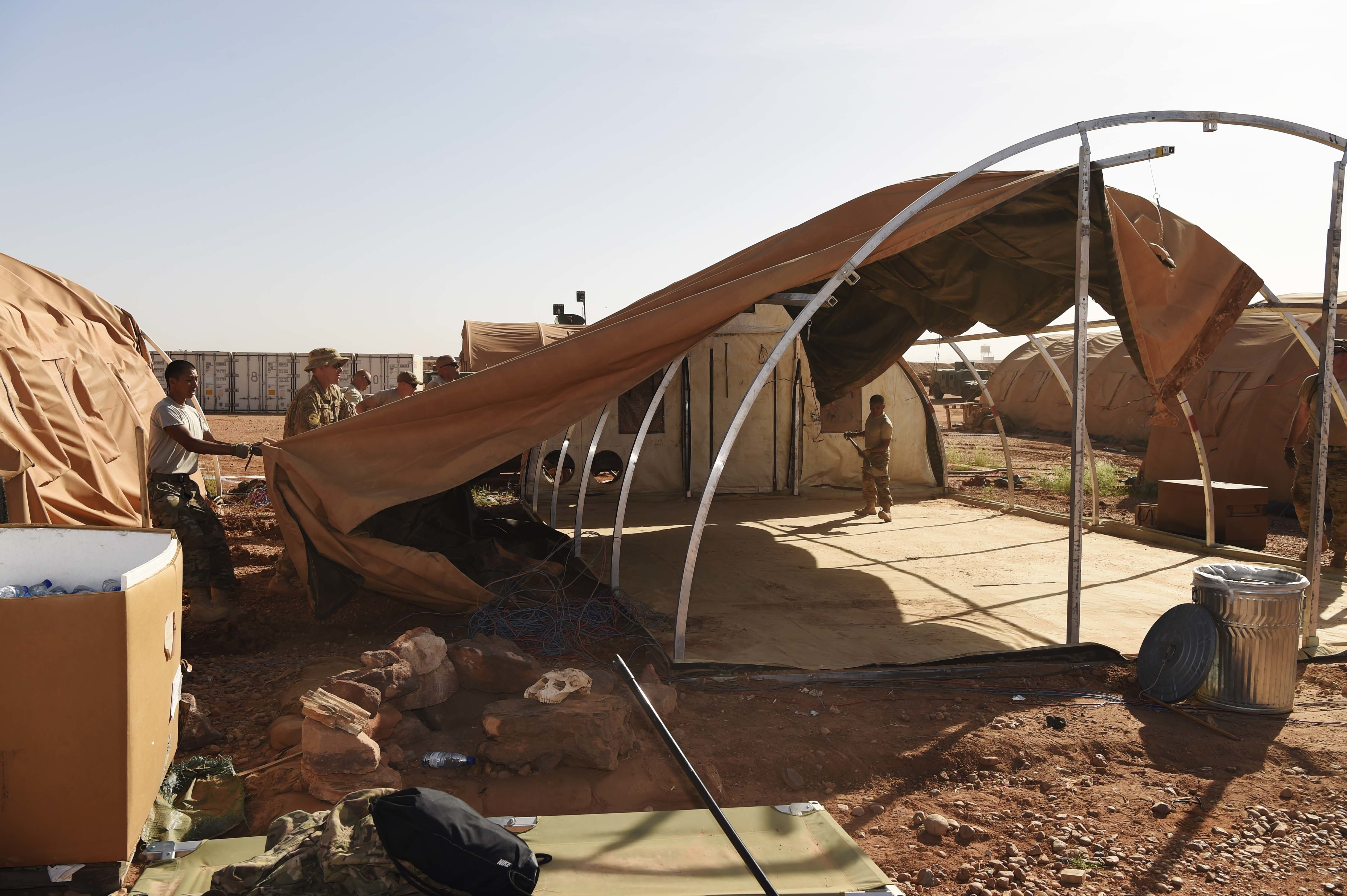 "Airmen from the 724th Expeditionary Air Base Squadron take down tents from the old base to move to a new location, Sept. 11, 2017, at Air Base 201, Agadez, Niger. The move to the bigger base is called ""FLEXIT,"" short for ""Flintlock Exit."" Being located in this deployed environment requires temporary housing in lieu of traditional infrastructure. (U.S. Air Force photo by Staff Sgt. Joshua R. M. Dewberry/released)"