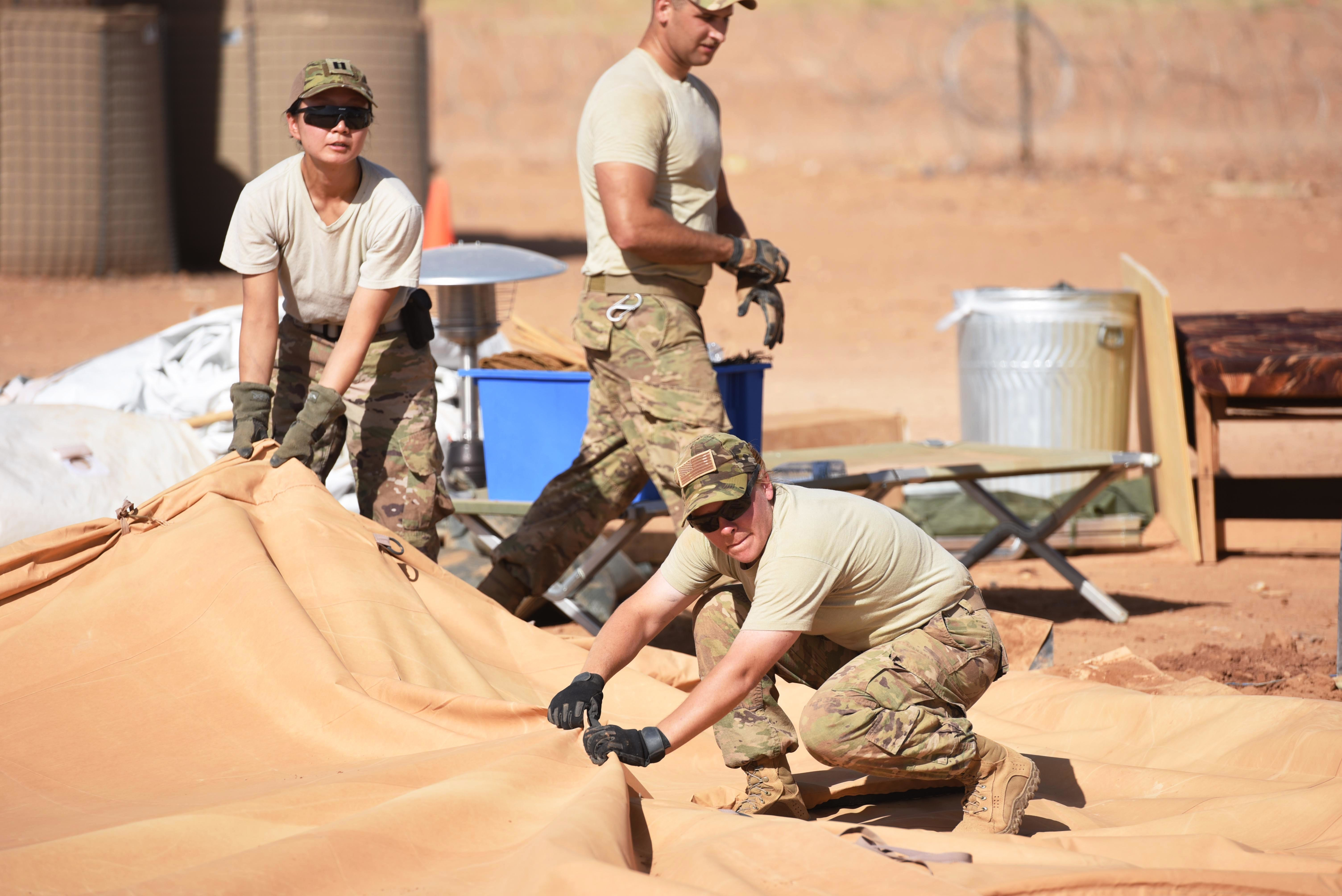 "Airmen from the 724th Expeditionary Air Base Squadron to work together to tear down tents from the old base to move to their new location, Sept. 11, 2017, at Air Base 201, Agadez, Niger. The move to the bigger base is called ""FLEXIT,"" short for ""Flintlock Exit."" Being located in this deployed environment requires temporary housing in lieu of traditional infrastructure. (U.S. Air Force photo by Staff Sgt. Joshua R. M. Dewberry/released)"