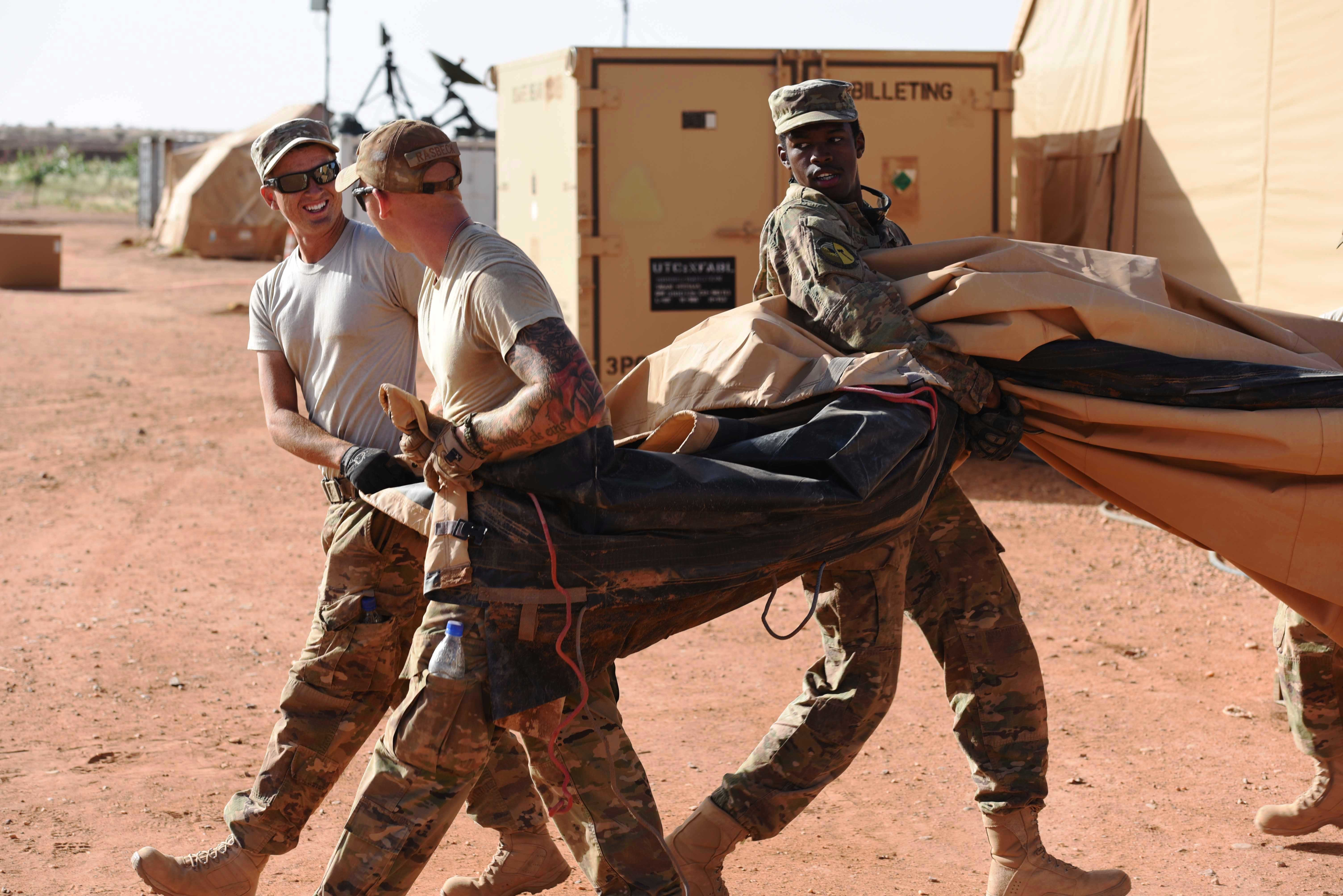 "Airmen from the 724th Expeditionary Air Base Squadron move the covers from tents from the old base to their new location, Sept. 11, 2017, at Air Base 201, Agadez, Niger. The move to the bigger base is called ""FLEXIT,"" short for ""Flintlock Exit."" Being located in this deployed environment requires temporary housing in lieu of traditional infrastructure. (U.S. Air Force photo by Staff Sgt. Joshua R. M. Dewberry/released)"