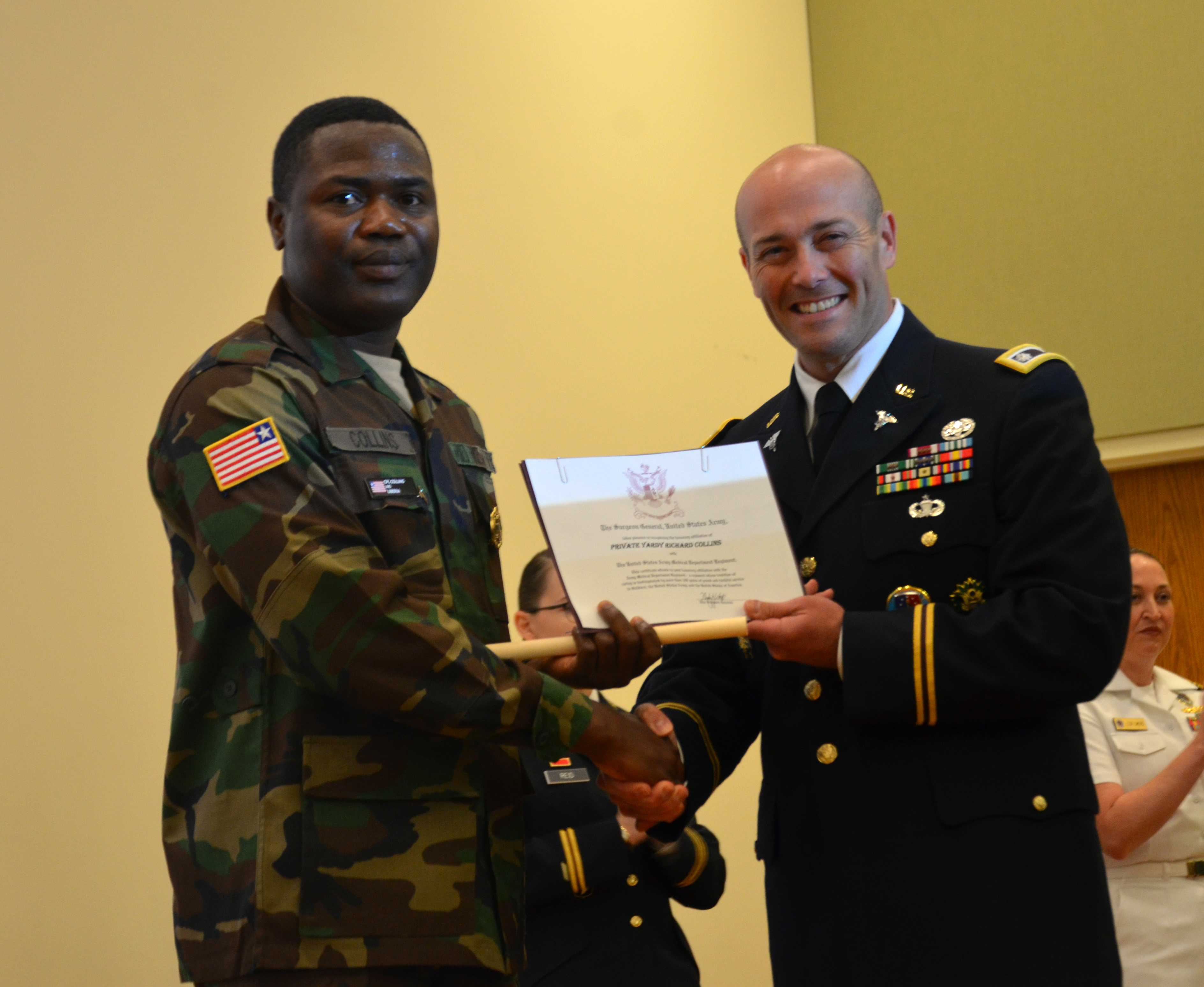Pfc. Yardy Collins, Liberian Armed Forces, receives a certificate from Lt. Col. Paul Lang, Army Service lead for the Medical Education and Training Campus preventive medicine specialist program, during the course graduation ceremony, October 20, 2017, making him an honorary member of the AMEDD regiment. Collins is the first international military student from Liberia to graduate from the program.