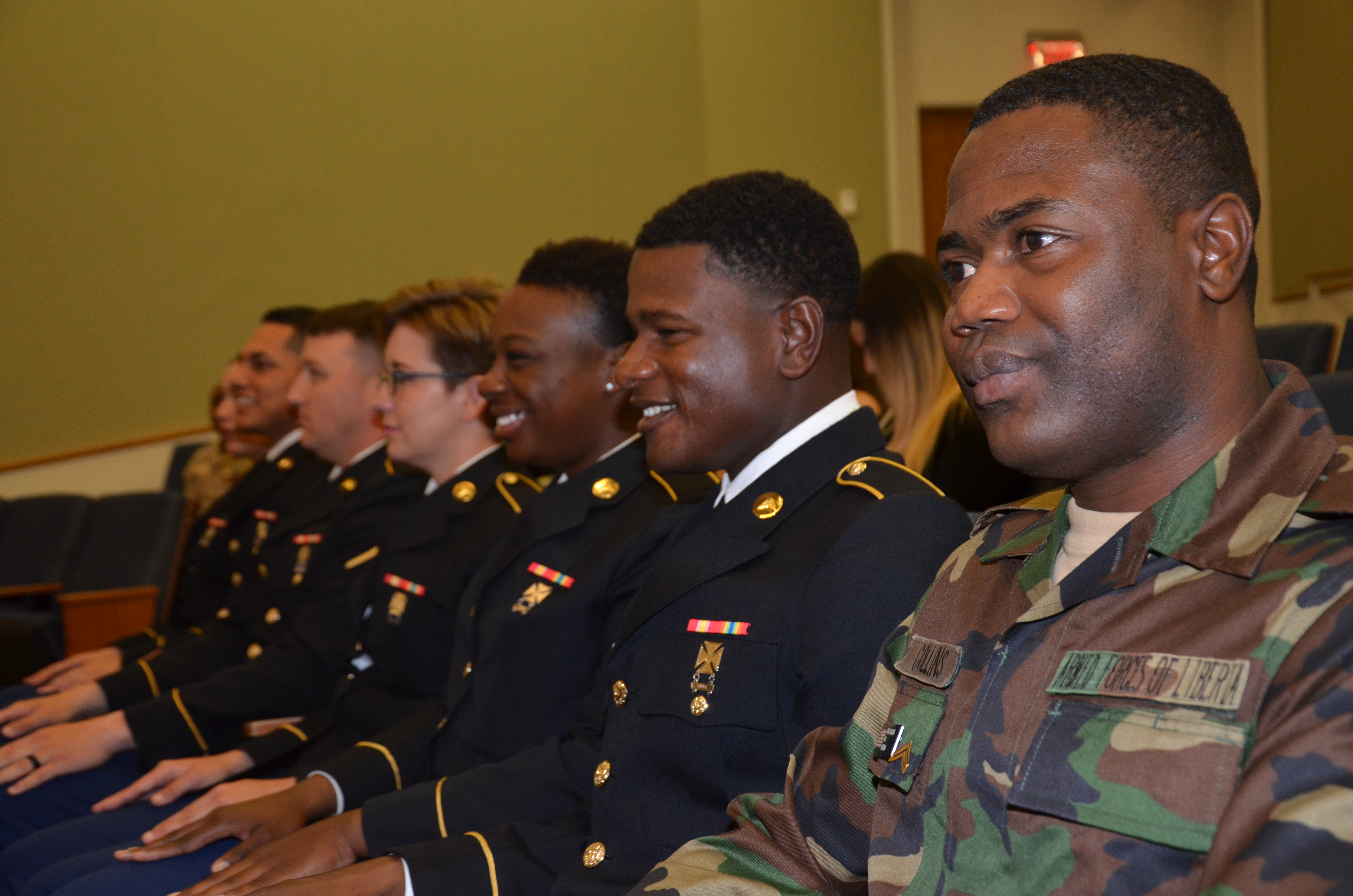 Pfc. Yardy Collins, Liberian Armed Forces, and his fellow classmates wait for the start of the Medical Education and Training Campus preventative medicine specialist graduation ceremony, Oct. 20, 2017. Collins is the first international military student from Liberia to graduate from the program.