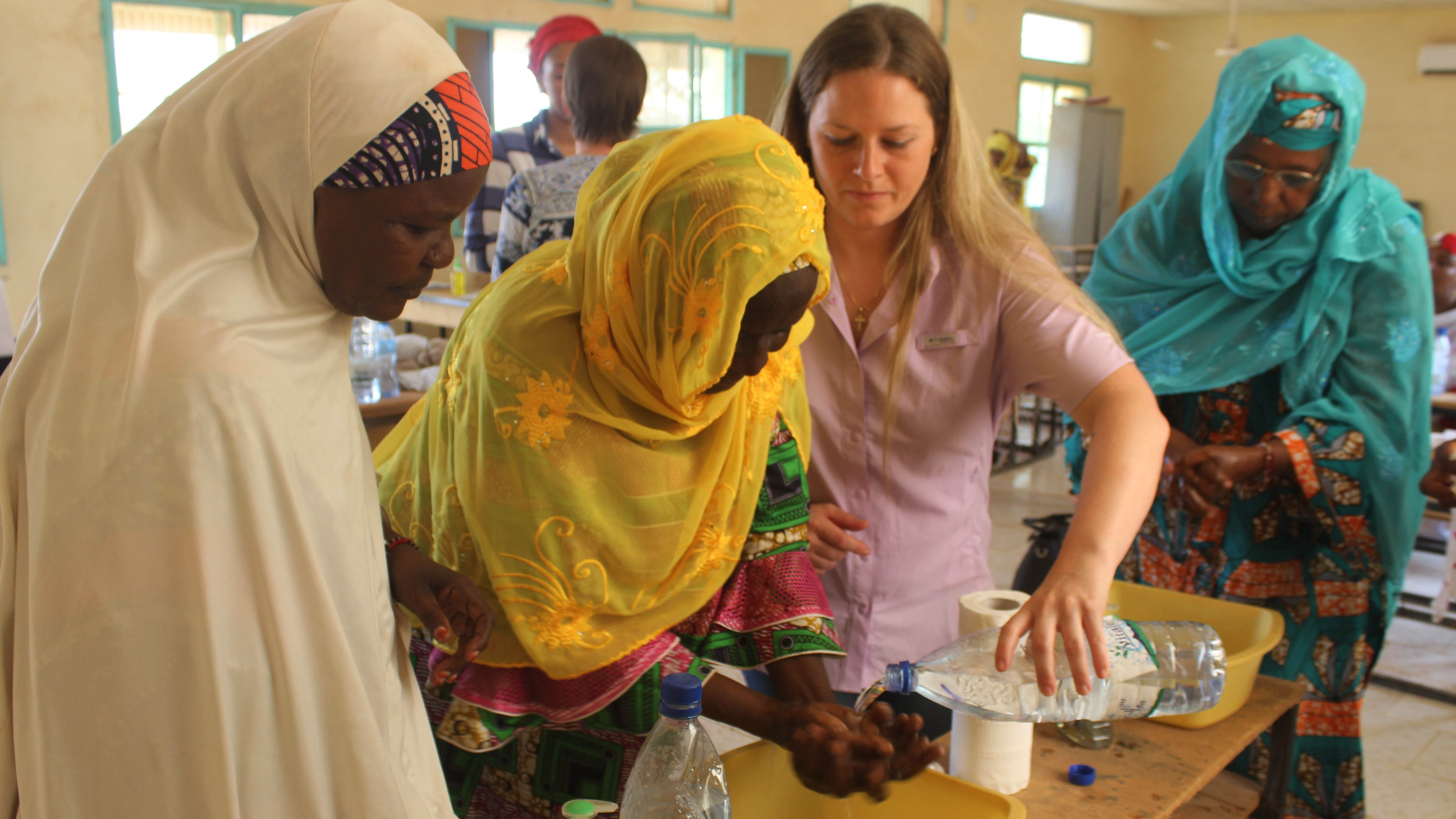 U.S. Air Force Tech. Sgt. Becky Smith (center right), 724th Expeditionary Air Base Squadron surgical technician, teaches basic hand washing methods during a women's hygiene class for the Association of Nigerien Women Against War on Aug. 14, 2017, in Agadez, Niger. Topics such as the importance of proper hygiene and how to combat communicable diseases were covered during the class. (Courtesy picture from the 724th Expeditionary Air Base Squadron medical section)