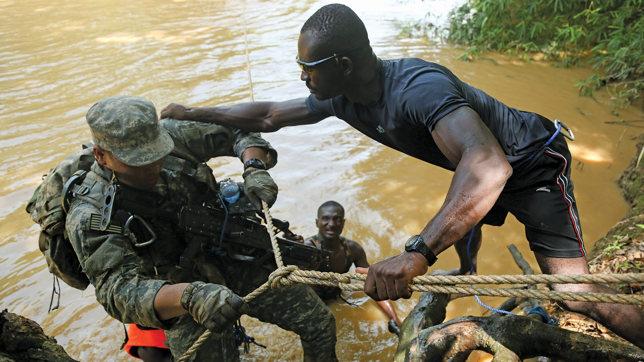 A Ghanaian Armed Forces trainer assists a U.S. soldier with the 101st Airborne Division (Air Assault) during an exercise in Ghana.