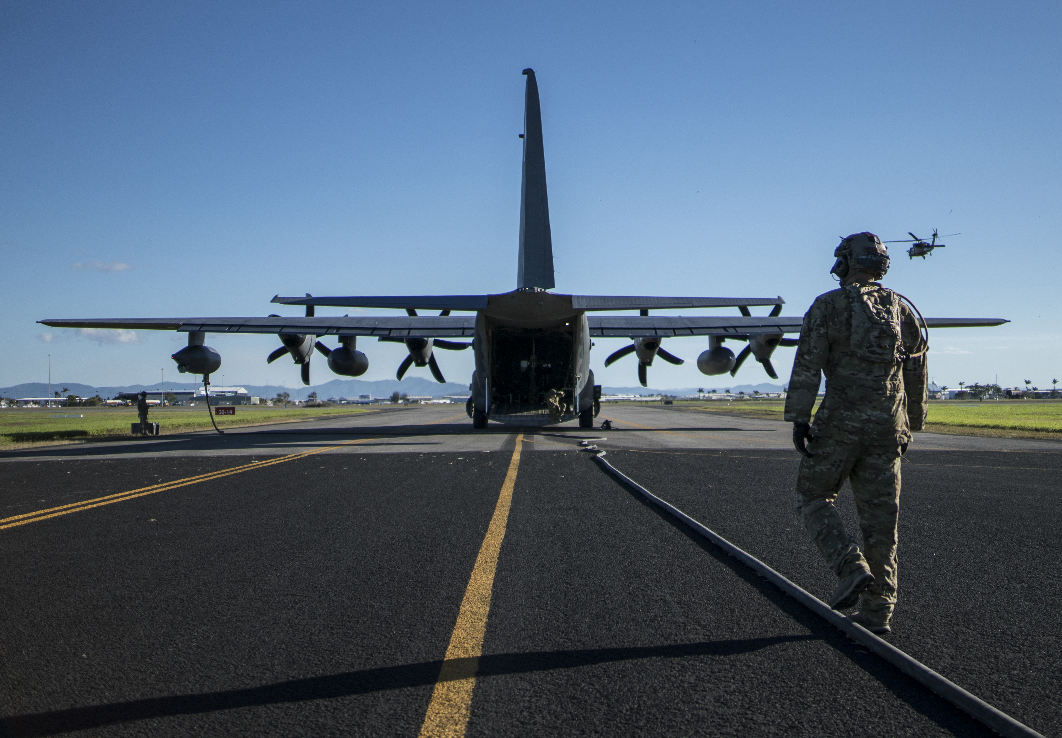 U.S. Air Force Tech. Sgt. Kade Bollinger follows the refueling hose back to the U.S. Air Force MC-130J Commando II following the forward air refueling point operations with five HH-60 Blackhawks from the 6th Aviation Assault Force July 17, 2017, at Mackay Field, Australia. (U.S. Air Force photo by Capt. Jessica Tait)