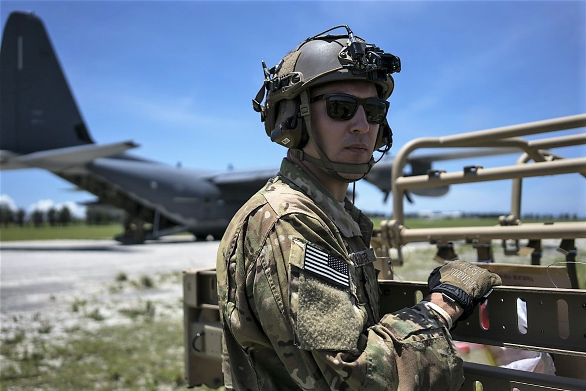 U.S. Air Force Tech. Sgt. Kade Bollinger stands postured to support the rapid infiltration and exfiltration of a tactical vehicle during a mass launch training mission June 22, 2017, at Ie Shima Range, Okinawa, Japan. (U.S. Air Force photo by Capt. Jessica Tait)