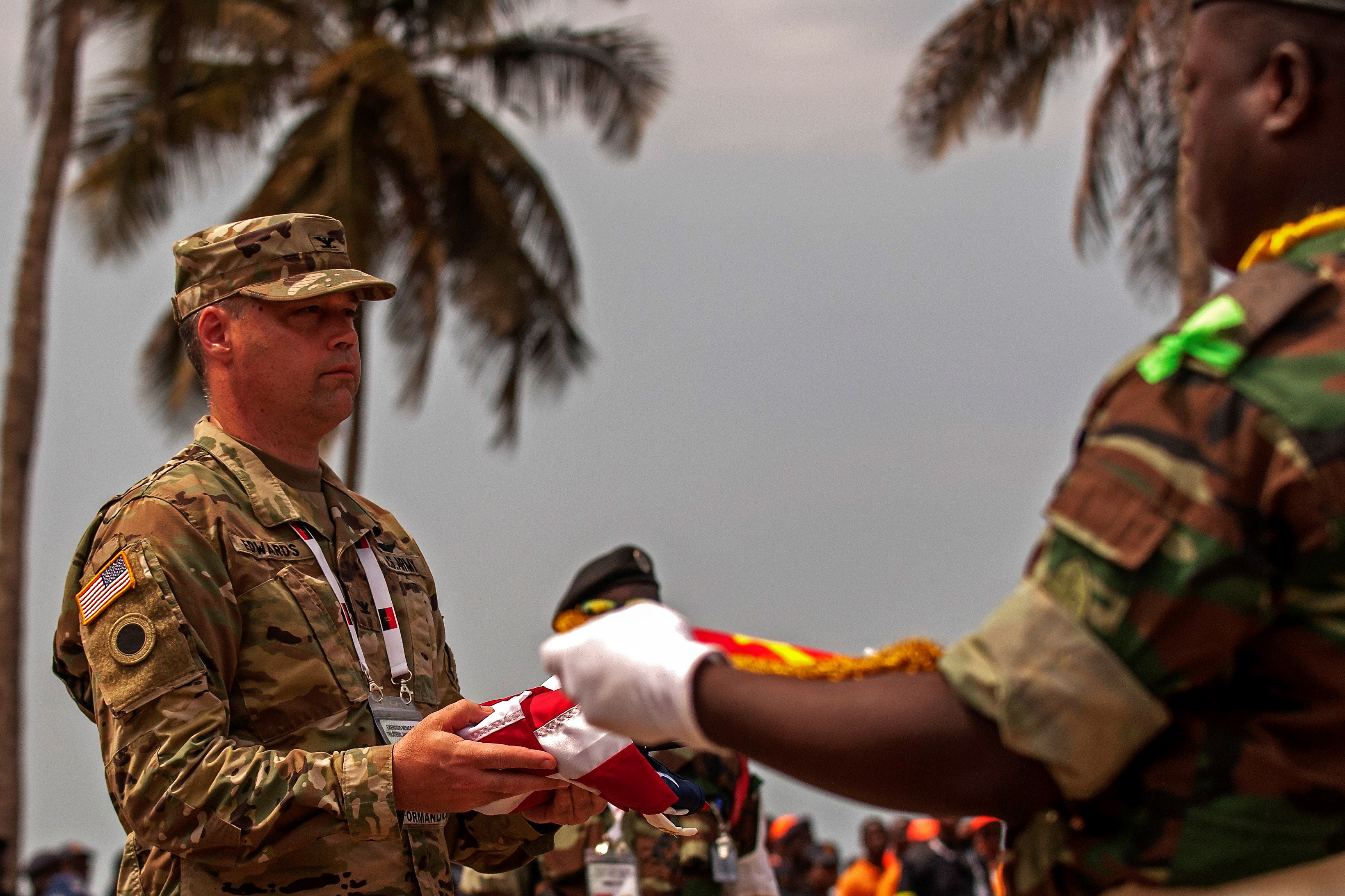 Col. Kevin Edwards, an Ohio Army National Guard nurse practitioner, accepts the U.S. flag during of the exchanging of flags at the VIP day and closing ceremony for PAMBALA 2017, Dec. 14, 2017, in Bengo Province, Angola. Personnel from the Serbian Armed Forces and the Ohio National Guard exchanged flags with their host nation, the Republic of Angola, and remarks were given by representatives of each participating country on the success of the first-ever trilateral engagement. (Ohio National Guard photo by Staff Sgt. Wendy Kuhn)