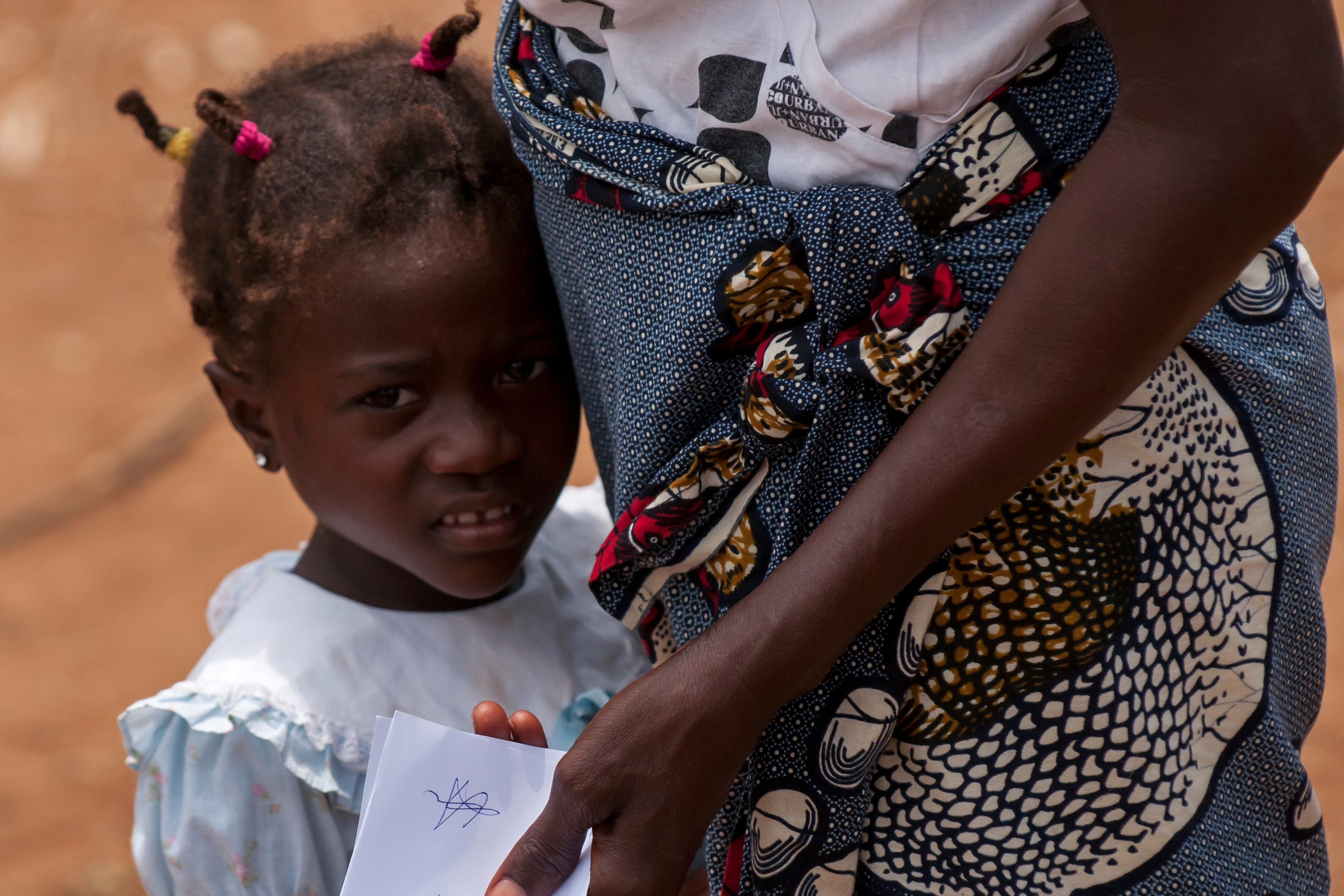 A child waits with her family outside one of the field hospital clinics in the village of Ceramica during the PAMBALA 2017 exercise Dec. 13, 2017, in Bengo Province, Angola. By participating in this trilateral medical engagement alongside the Angolan and Serbian Armed Forces, the Ohio National Guard is gaining real-world experience and training on tropical diseases while also providing valuable coaching and mentorship on disease management and containment. (Ohio National Guard photo by Staff Sgt. Wendy Kuhn)