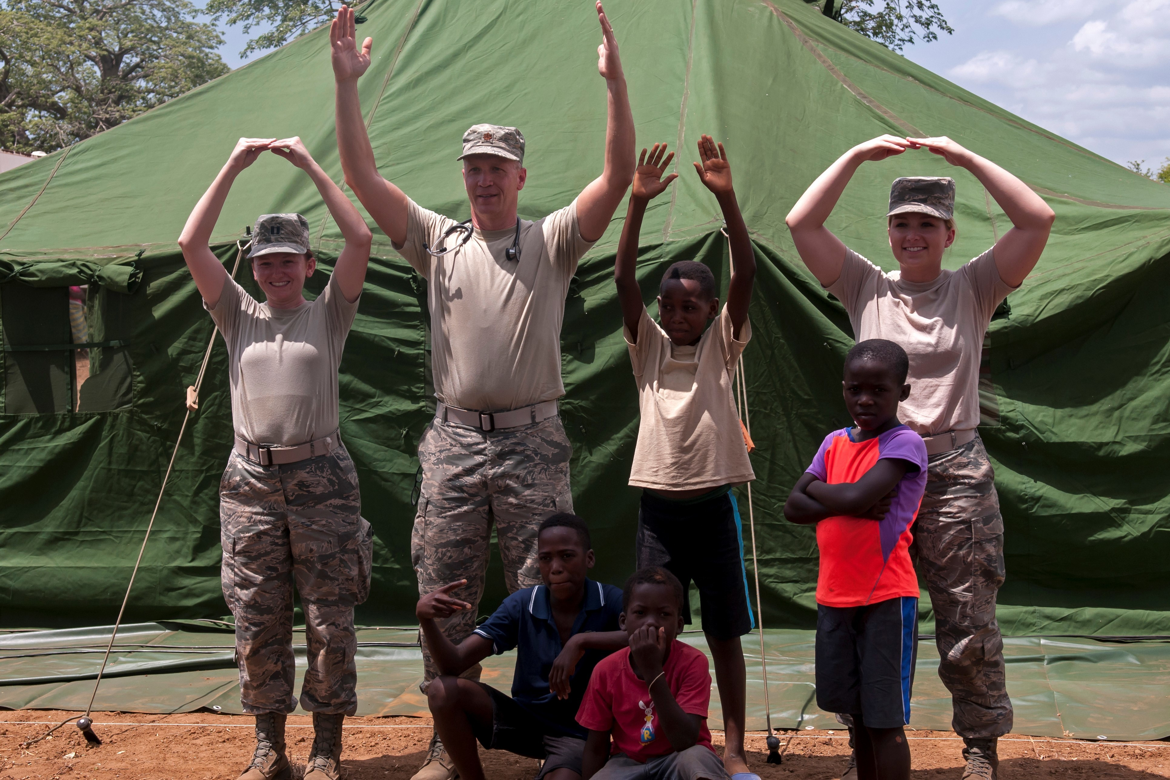 "Ohio Air National Guard members Capt. Sarah Woodson (from left), Maj. Adam Bihl and Senior Airman Hannah Halcomb play with children in the village of Ceramica and show some state pride by forming the ""O-H-I-O""  the PAMBALA 2017 exercise Dec. 13, 2017, in Bengo Province, Angola, Dec. By participating in this trilateral medical engagement alongside the Angolan and Serbian Armed Forces, the Ohio National Guard is gaining real-world experience and training on tropical diseases while also providing valuable coaching and mentorship on disease management and containment. This engagement is the first of its kind to take place in the Republic of Angola and is part of a trilateral agreement between Angola, Serbia and the U.S. (Ohio National Guard photo by Staff Sgt. Wendy Kuhn)"