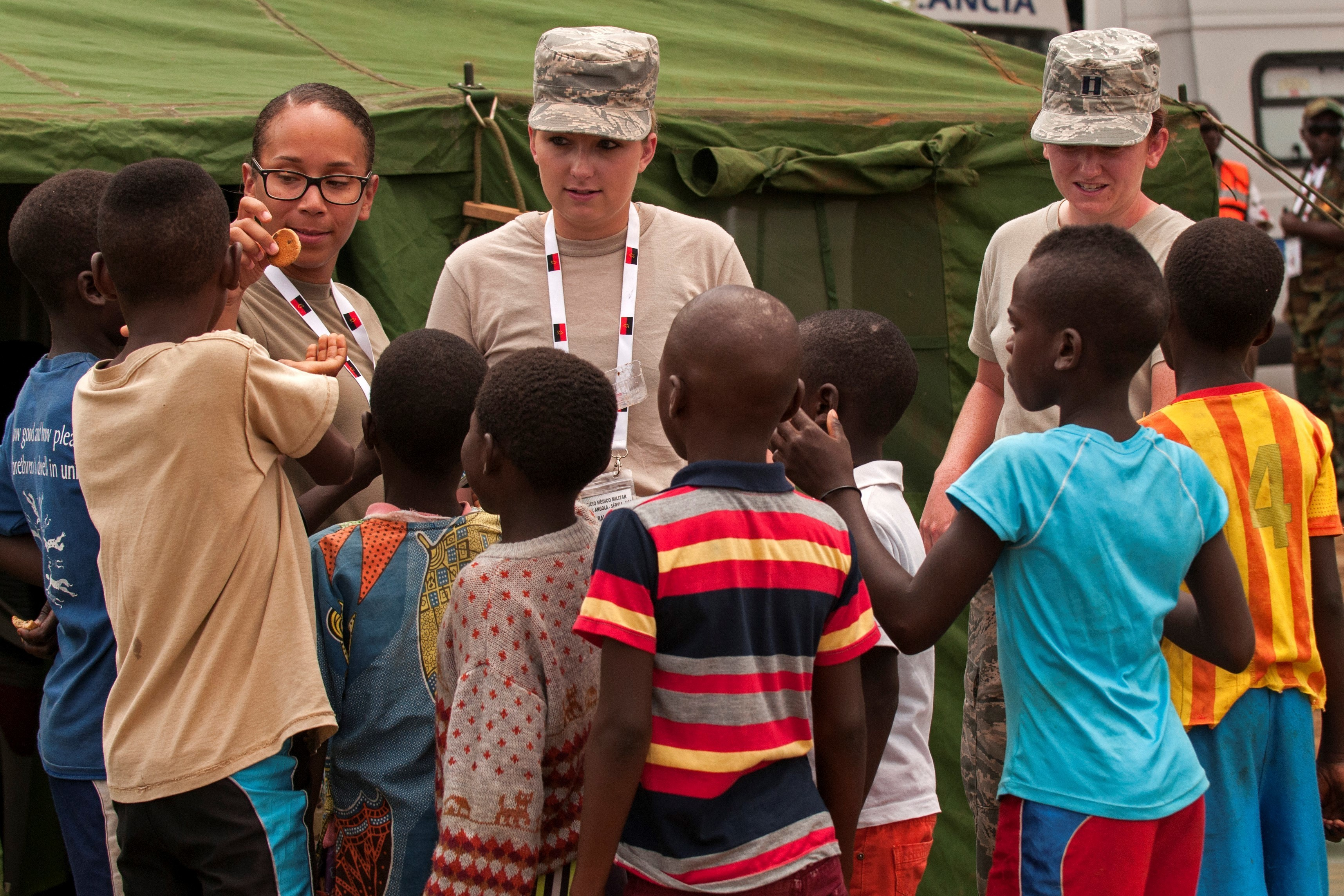 Staff Sgt. Ashley Maldonado (from left), Senior Airman Hannah Halcomb and Capt. Sarah Woodson from the Ohio National Guard pass out snacks to children in the village of Ceramica during the PAMBALA 2017 exercise Dec. 13, 2017, in Bengo Province, Angola. By participating in this trilateral medical engagement alongside the Angolan and Serbian Armed Forces, the Ohio National Guard is gaining real-world experience and training on tropical diseases while also providing valuable coaching and mentorship on disease management and containment. Ohio has been paired with the Republic of Serbia since 2006 through the National Guard State Partnership Program. (Ohio National Guard photo by Staff Sgt. Wendy Kuhn)