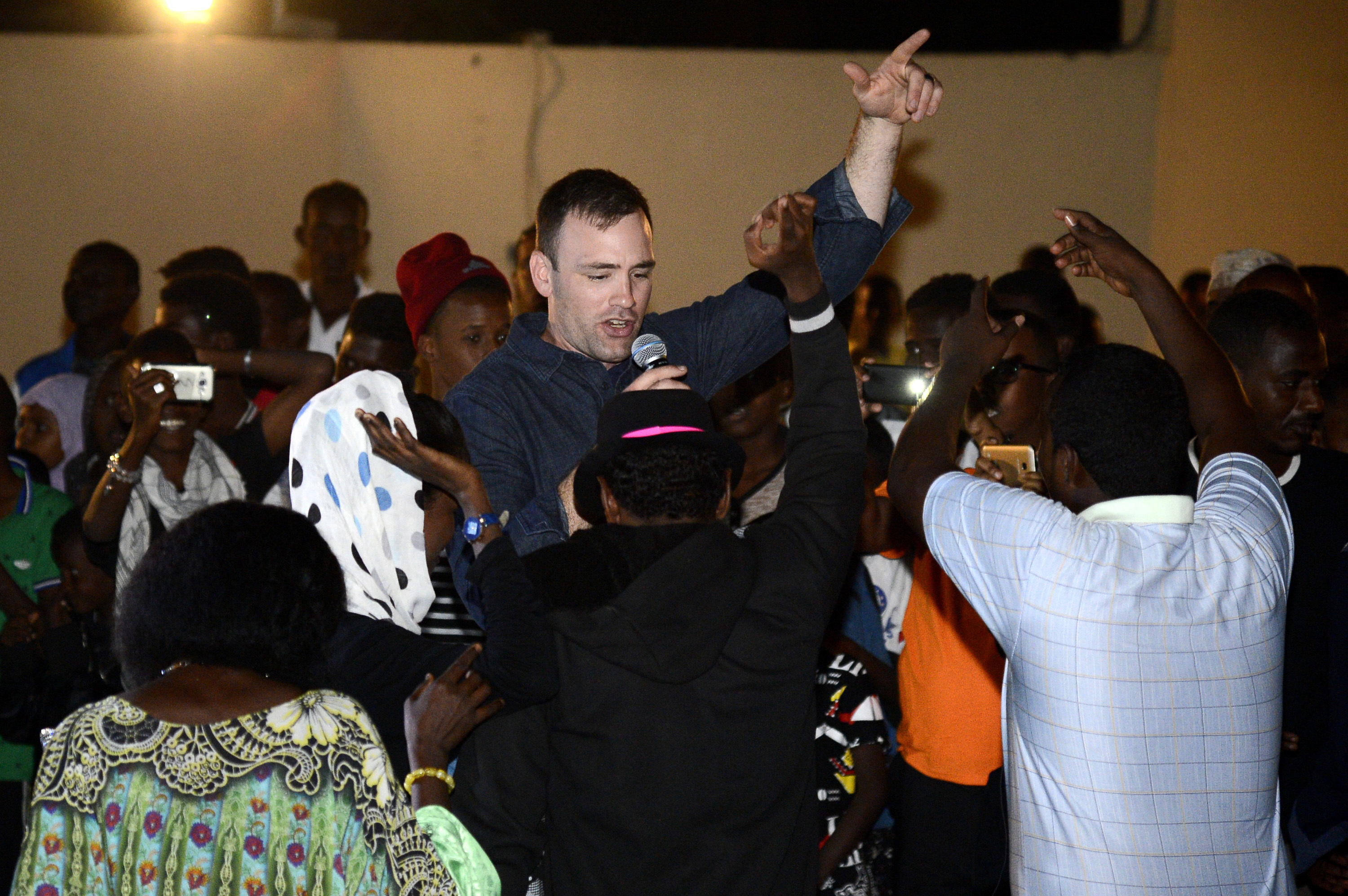 U.S. Air Force Staff Sgt. Craig Larimer, a member of the U.S. Air Forces Central Command (AFCENT) Band, sings and dances with Djiboutians during a concert at the Balbala E-Learning Center in Djibouti, January 10, 2018. The AFCENT Band performed at the E-Learning center as part of their two week tour where they held workshops, clinics, and concerts throughout the city of Djibouti. (U.S. Navy Photo by Mass Communication Specialist 2nd Class Timothy M. Ahearn/Released)