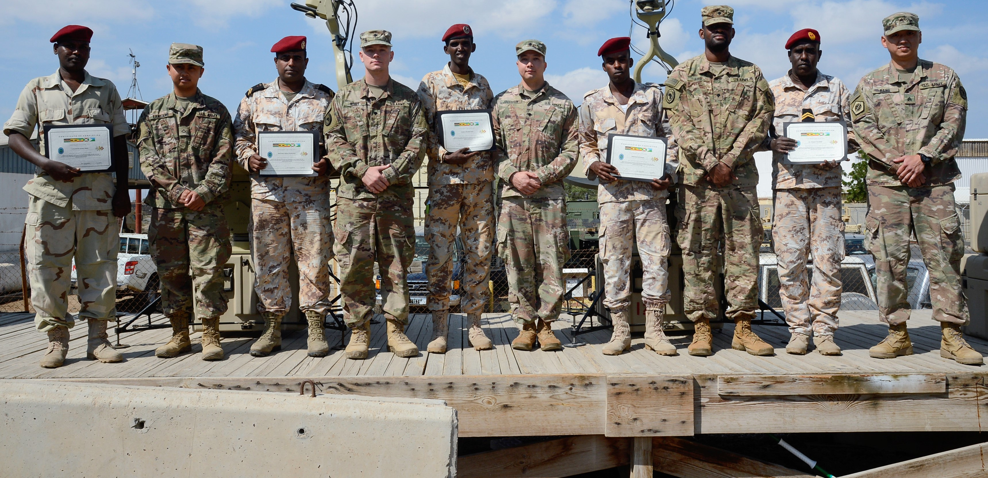 U.S. Soldiers assigned to the Combined Joint Task Force - Horn of Africa (CJTF-HOA) Communications Directorate and members of the Djibouti Armed Forces pose for a photo after completing a military-to-military exchange course at Camp Lemonnier, Djibouti, Jan. 17, 2018. Throughout a two-week period, communications experts advised Djiboutian service members on how to set up, operate, maintain, and troubleshoot network equipment to increase communication capabilities between African Union Mission in Somalia forces. (U.S. Navy photo by Mass Communications Specialist 2nd Class Timothy M. Ahearn)