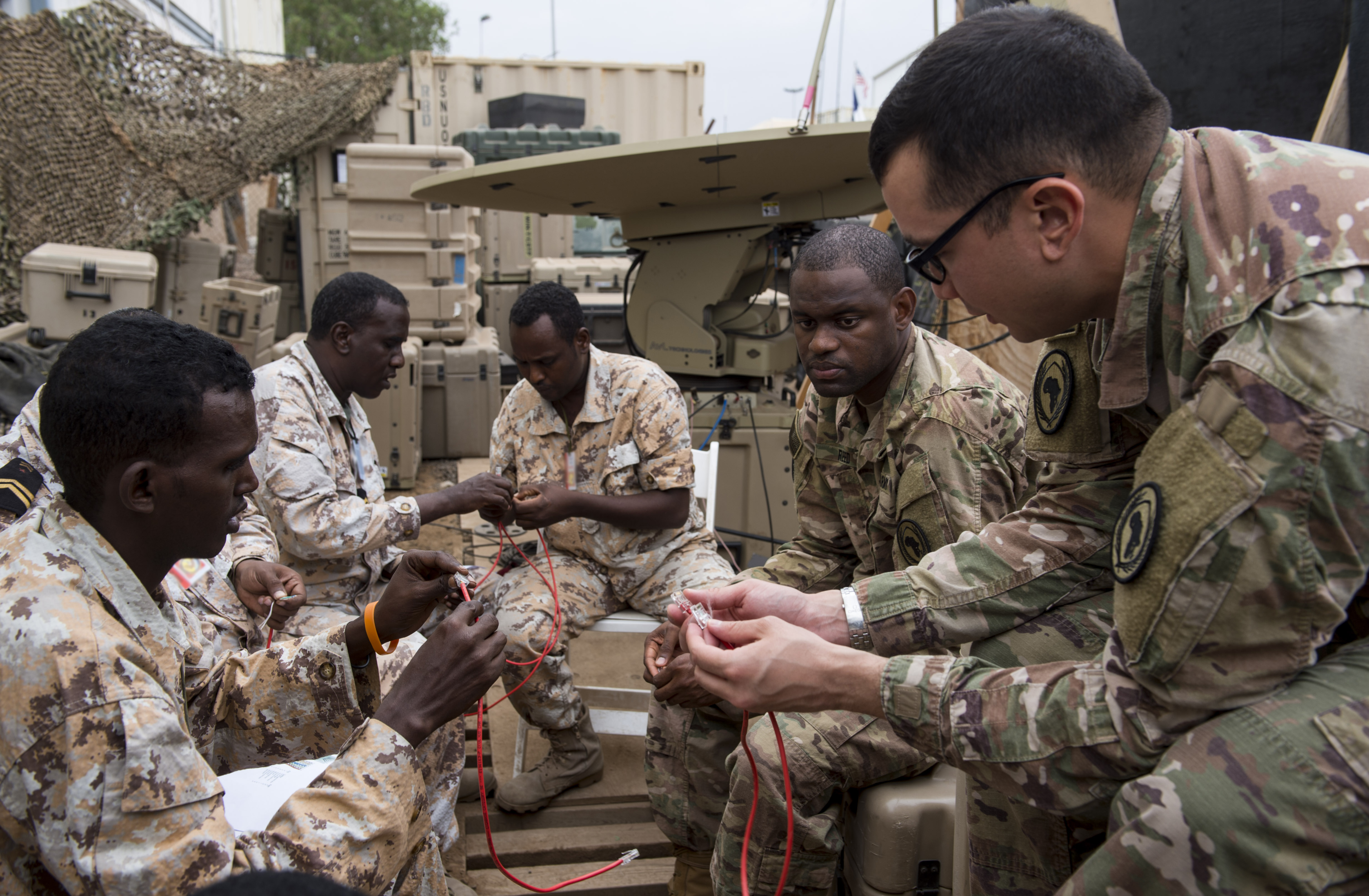 U.S. Army Spc. Matthew Jousselin, right, a multisystem transmission operator and maintainer assigned to the Combined Joint Task Force - Horn of Africa (CJTF-HOA) Communications Directorate, explains how to arrange the wires in a cable to a Djibouti Armed Forces (FAD) member during a military-to-military exchange course at Camp Lemonnier, Djibouti, Jan. 10, 2018. Throughout a two-week period, communications experts advised Djiboutian service members on how to set up, operate, maintain, and troubleshoot network equipment to increase communication capabilities between African Union Mission in Somalia forces. (U.S. Air Force photo illustration by Staff Sgt. Timothy Moore)