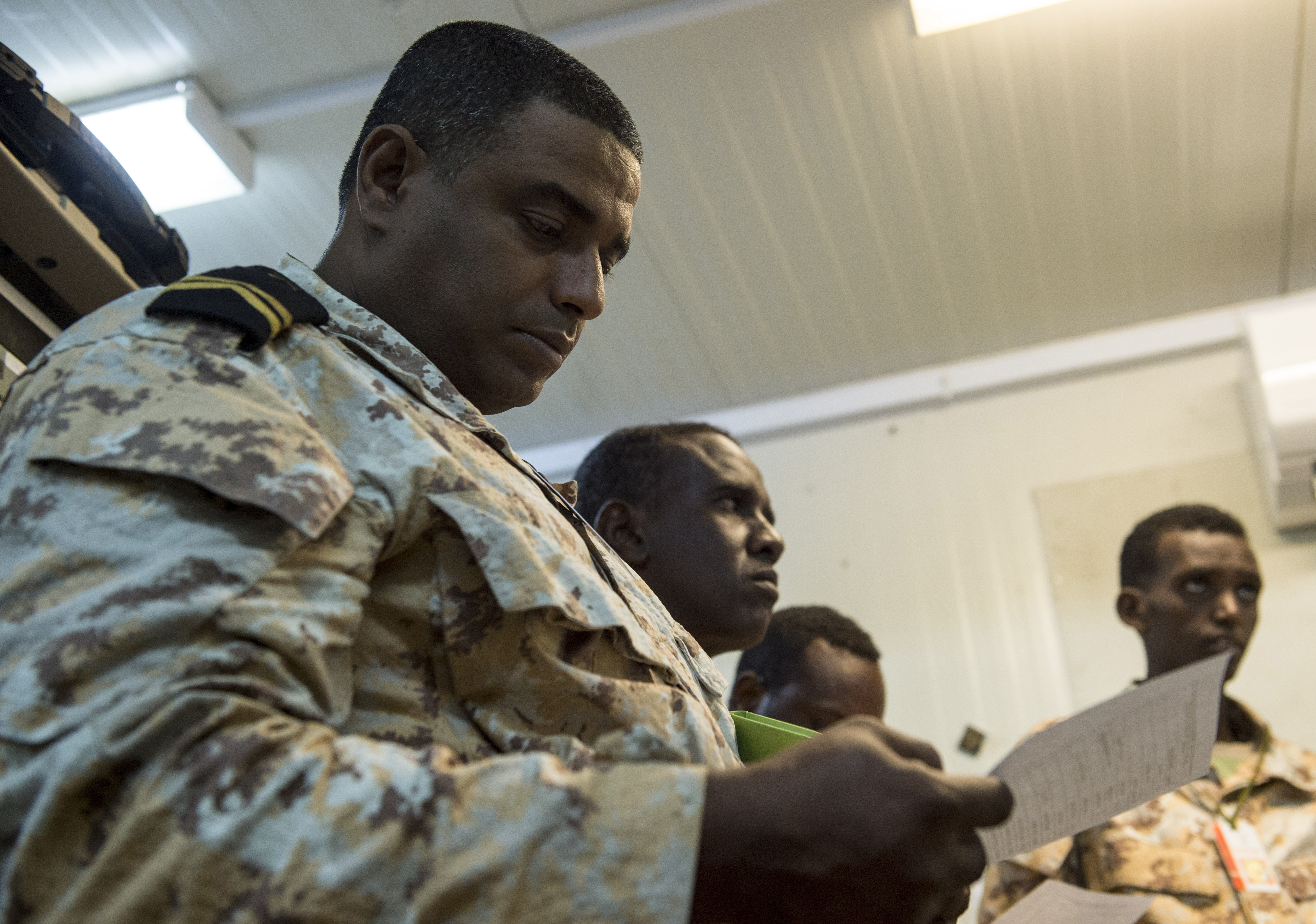 A Djibouti Armed Forces (FAD) member reviews a sheet of input commands during a military-to-military exchange course with U.S. Soldiers assigned to the Combined Joint Task Force - Horn of Africa (CJTF-HOA) Communications Directorate, at Camp Lemonnier, Djibouti, Jan. 9, 2018. Throughout a two-week period, communications experts advised Djiboutian service members on how to set up, operate, maintain, and troubleshoot network equipment to increase communication capabilities between African Union Mission in Somalia forces. (U.S. Air Force photo illustration by Staff Sgt. Timothy Moore)