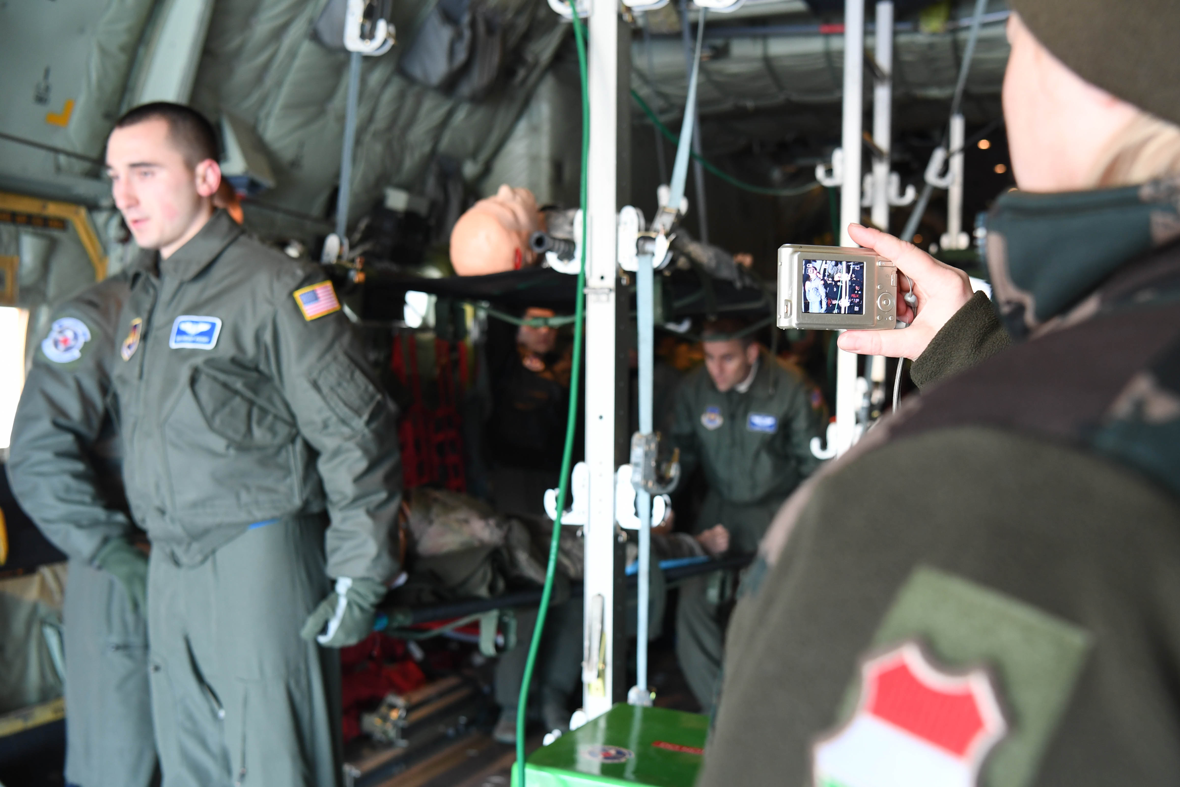 Hungarian air force 2nd Lt. Anita Huszarik takes a video of U.S. Air Force aeromedical team members demonstrating a patient being off-loaded on a C-130J Super Hercules at Ramstein Air Base, Germany, Jan. 18, 2018. Military aeromedical teams attended a week-long Partnership Flight Symposium to discuss aeromedical evacuation tactics, techniques and procedures while strengthening cooperation and enhancing relationships between African, European and United States military medical systems. (U.S. Air Force photo by Tech. Sgt. Rachelle Coleman)