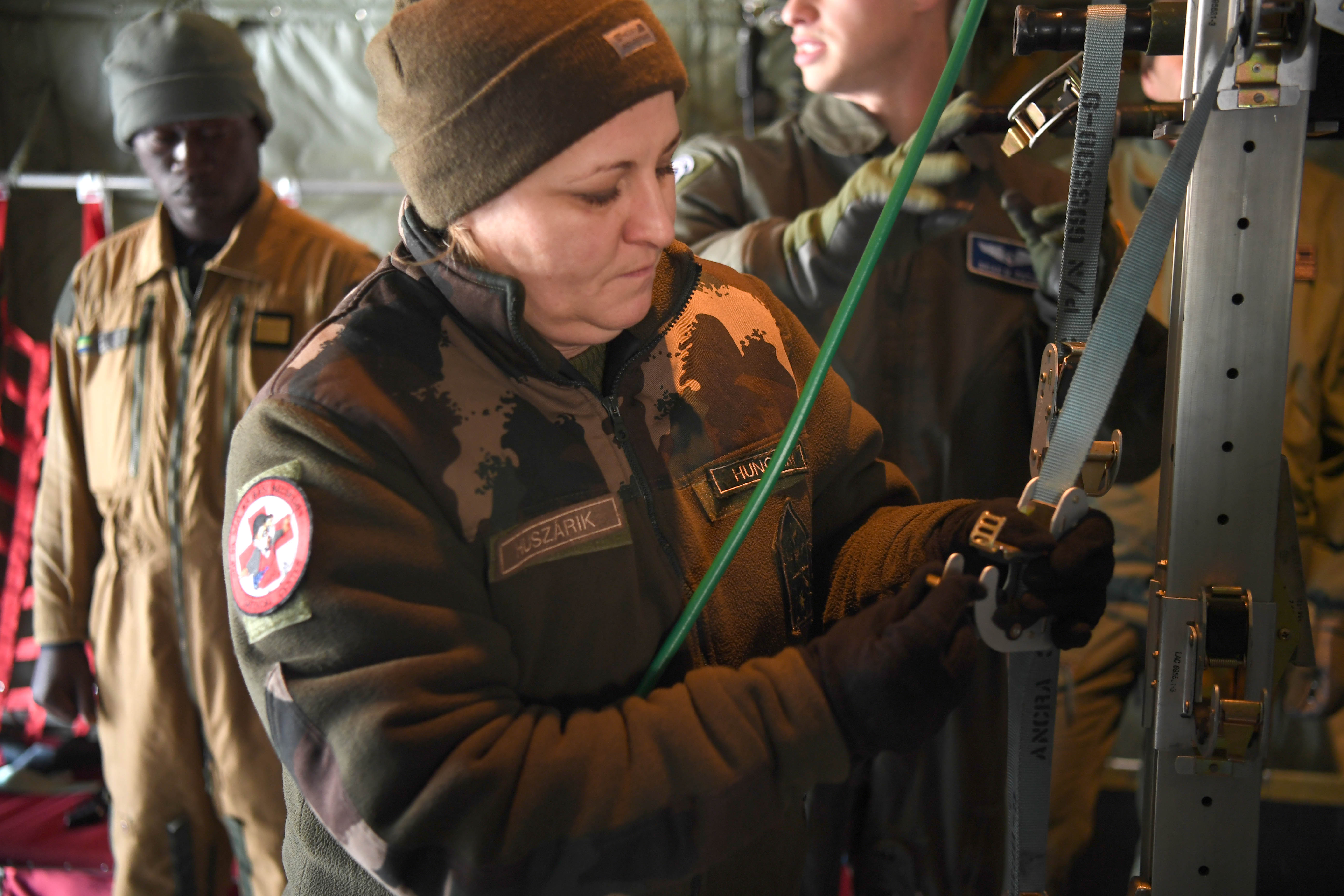 Hungarian air force 1st Lt. Anita Huszarik studies a hanging strap used to secure litter patients on a C-130J Globemaster III at Ramstein Air Base, Germany, Jan. 18, 2018. The C-130 is capable of carrying a large number of litter patients and a five-person aeromedical evacuation crew in a crisis situation. (U.S. Air Force photo by Tech. Sgt. Rachelle Coleman)