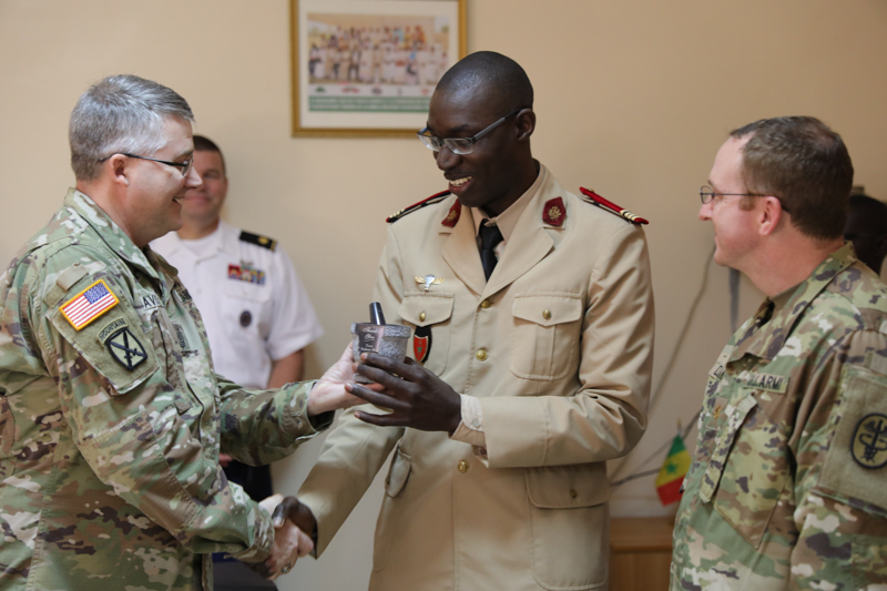 U.S. Army Sgt. Maj. Michael Davis and Maj. Richard Delaney recognize Senegalese Commandant Balla Diop, Feb. 22, 2018, for his assistance in coordinating MEDRETE 18-1, during a ceremony held at Hospital Militaire De Ouakam, Dakar, Senegal. MEDRETE is a combined effort between the Senegalese government, U.S. Army Africa, and the Vermont National Guard. MEDRETE 18-1 is the first in a series of medical readiness training exercises that U.S. Army Africa is scheduled to facilitate within various countries in Africa, and serves as an opportunity for the partnered militaries to hone and strengthen their general surgery and trauma skills while reinforcing the partnership between the countries. The mutually beneficial exercise brings together Senegalese military and U.S. Army medical professionals to foster cooperation while conducting medical specific tasks. (U.S. Army photo by Sgt. Micah Merrill)