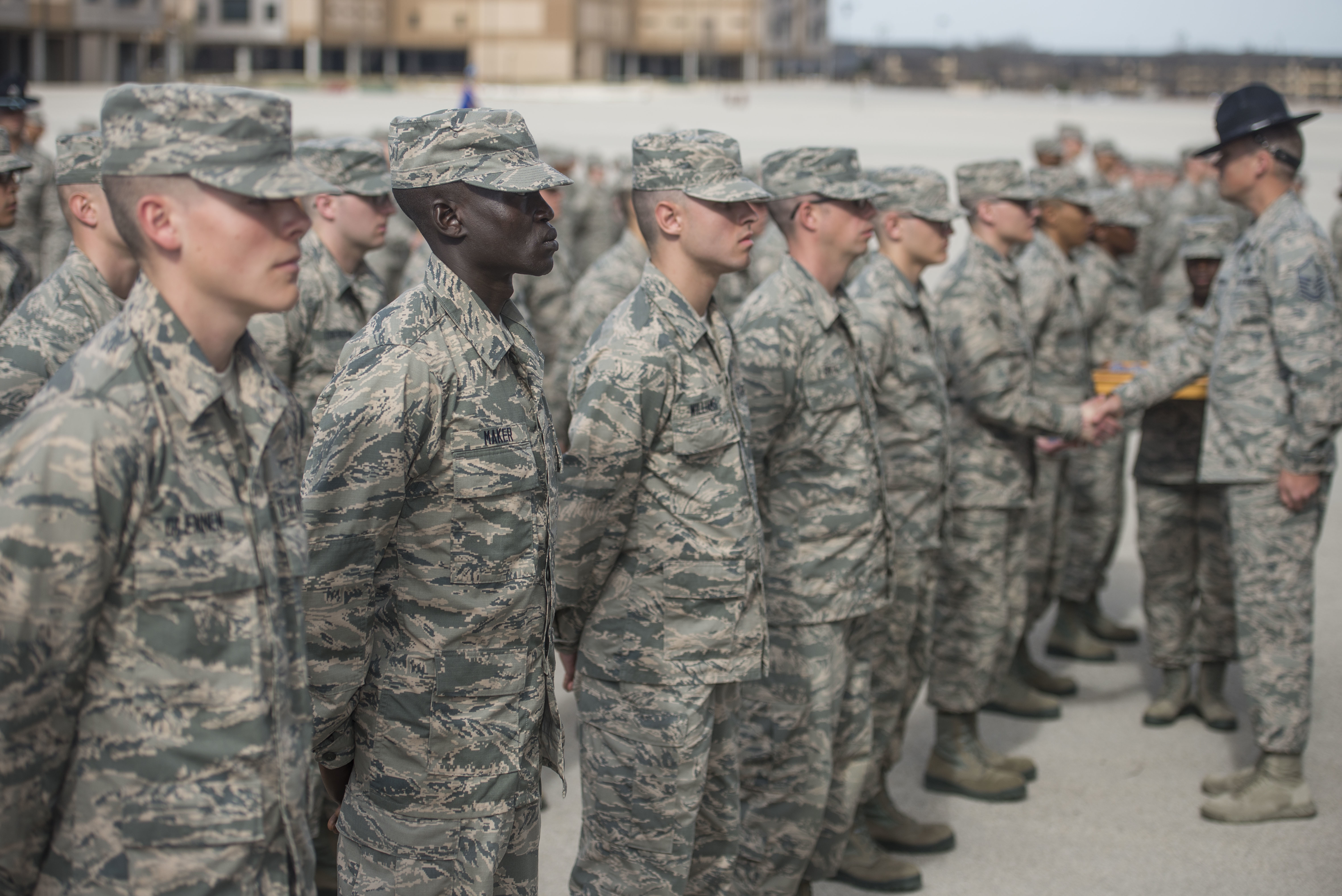 "Guor Maker, a trainee at Air Force Basic Military Training, stands in formation at the Coin Ceremony Feb. 1, 2018 outside the Pfingston Reception Center at Joint Base San Antonio-Lackland, Texas. During the BMT Coin Ceremony Trainees are given ""Airman's Coins' signifying the final transition from trainee to Airman."