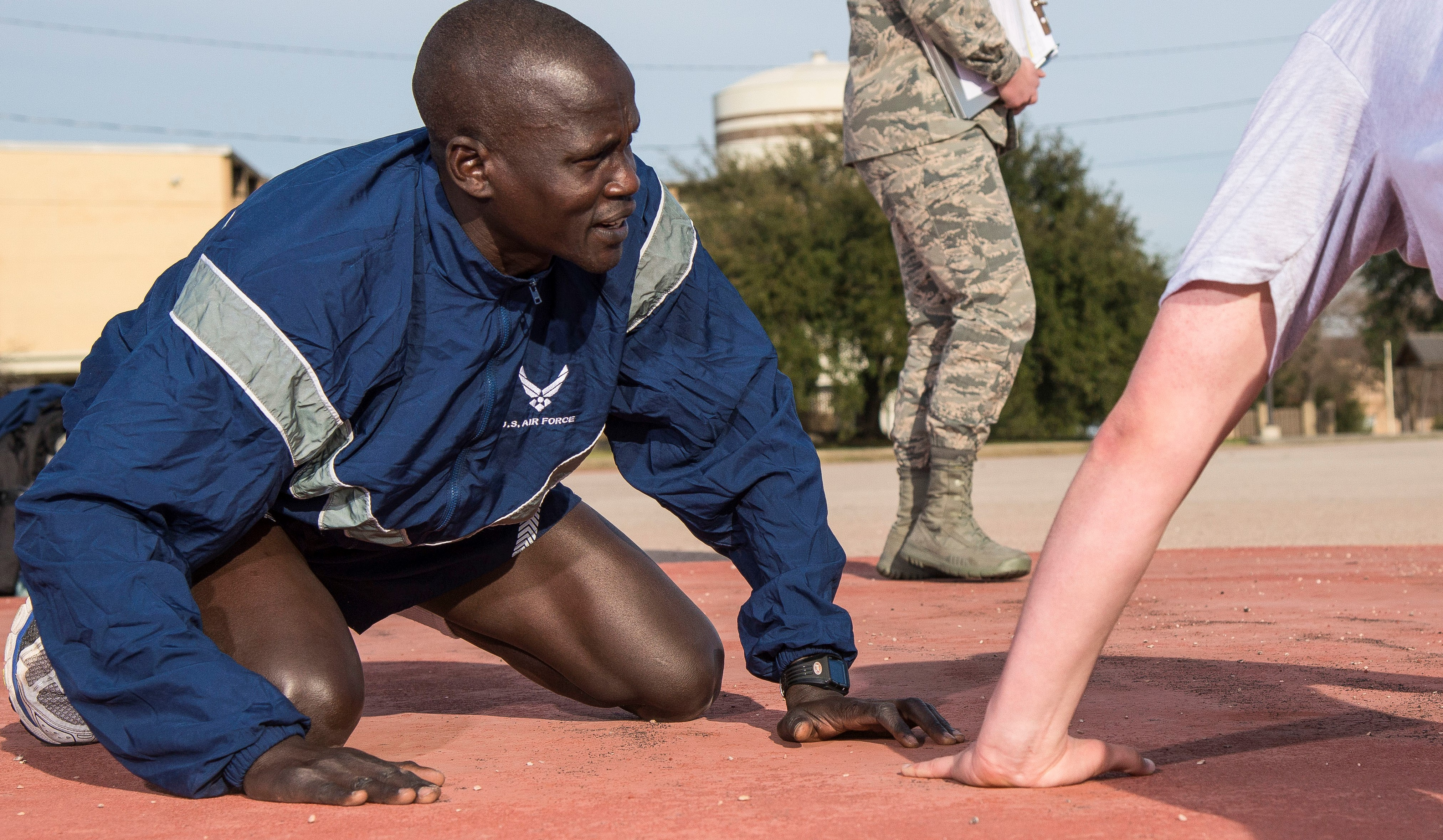 Guor Maker, a trainee at Air Force Basic Military Training, supports a wingman taking a physical fitness test Jan. 30, 2018 at the 324th Training Squadron's physical training pad at Join Base San Antonio-Lackland, Texas. Maker was selected as a physical training leader for his time at BMT, his duties include leading the flight during warm-ups and providing support for struggling trainees.
