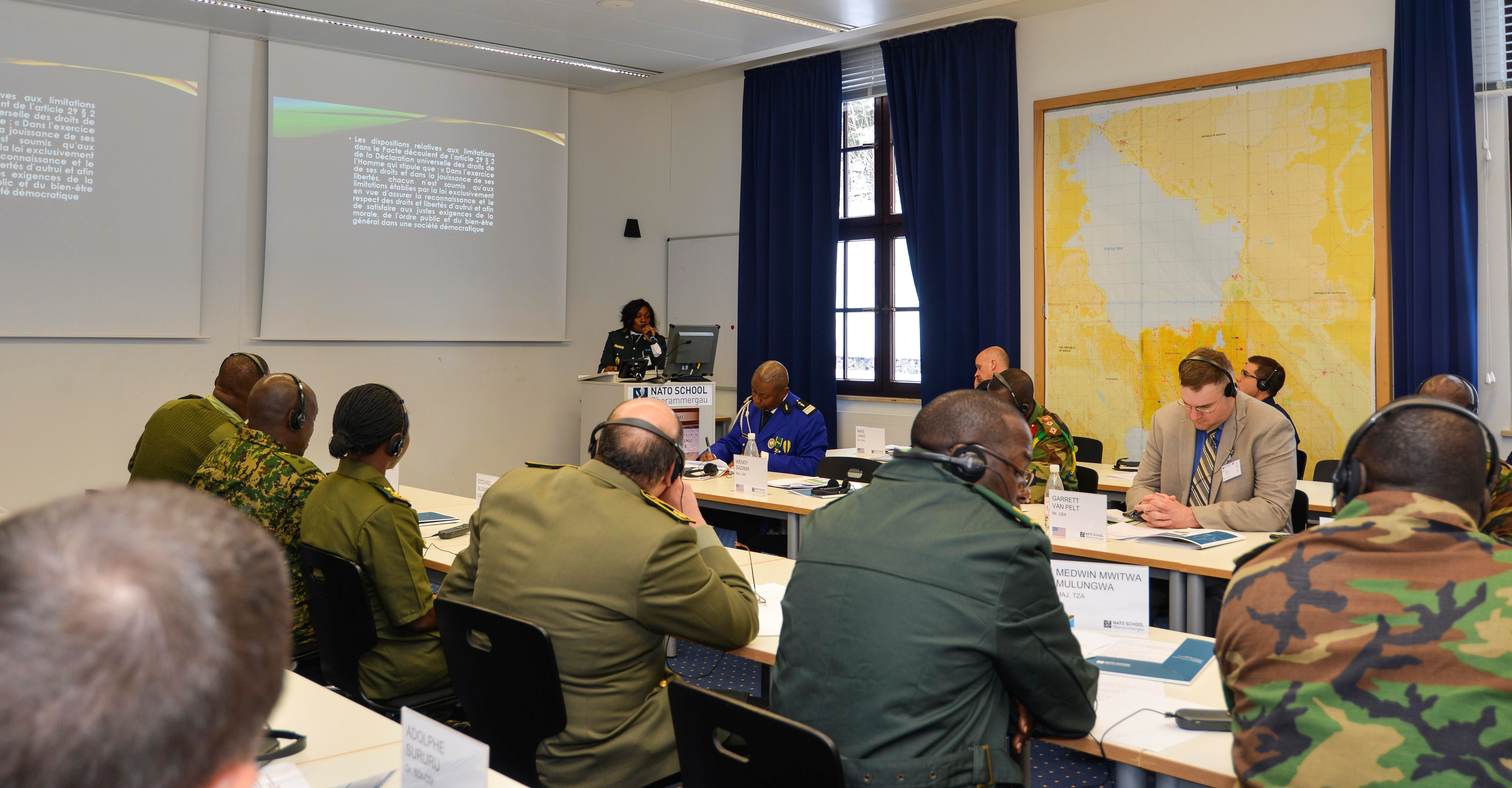 Africa Military Law Forum Co-Chairwoman Lt. Col. Marguerite Meffand Loaw, (standing at podium in background) current president of the Cameroon Military Tribunal, describes terrorism prosecutions and the institutional safeguards which exist in Cameroon to insure a fair trial, Oberammergau, Germany, March 1, 2018. (Photo by Cpl. Victor Leonard, NATO School Public Affairs/Released)
