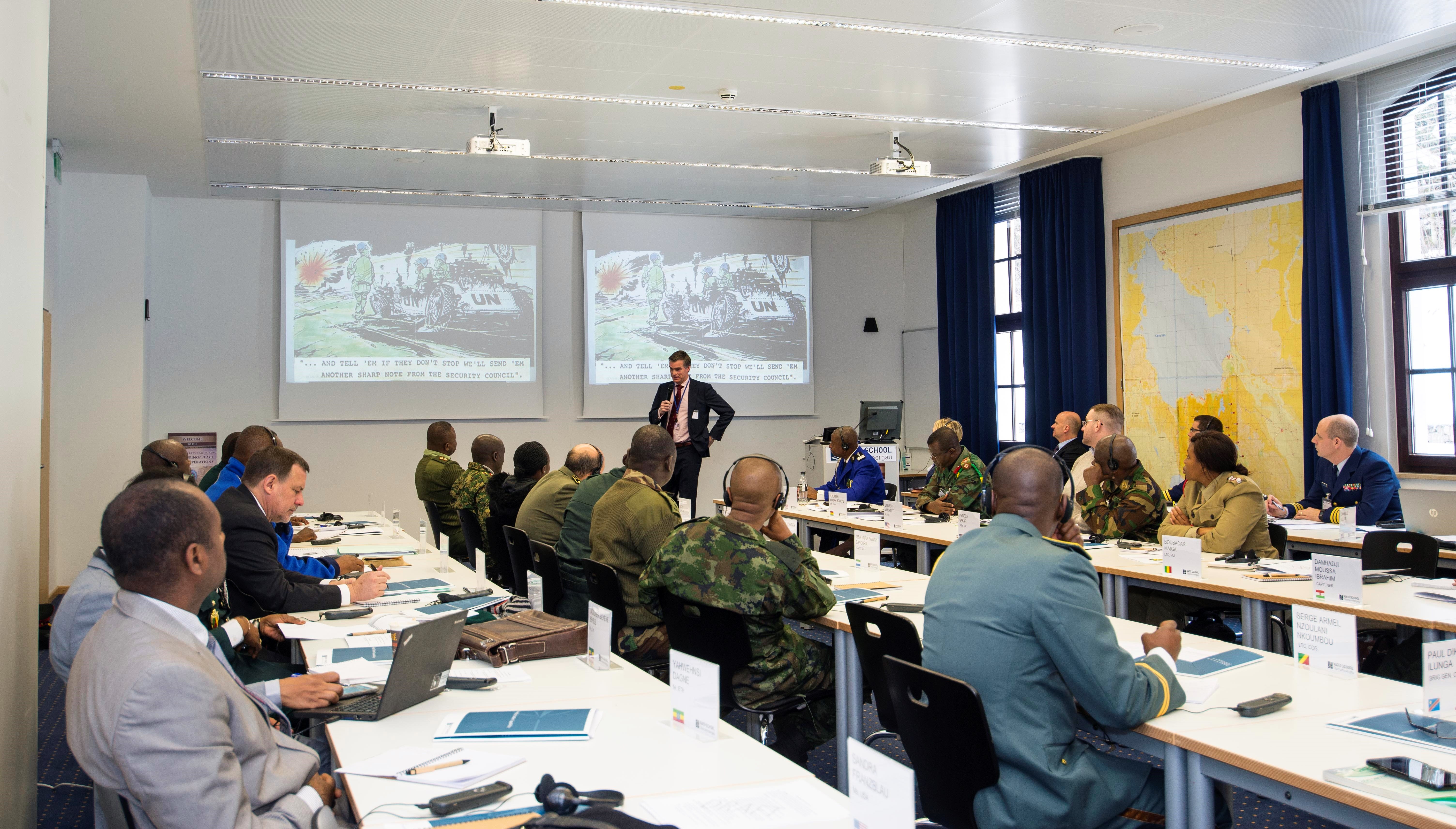 Col. (ret.) Benardus Klappe (standing in the background) of the Military Law and Law of War Society, delivers a presentation on investigations within the peace operations context, with a focus on protection of civilian mandates, Oberammergau, Germany, March 1, 2018. (Photo by Cpl. Victor Leonard, NATO School Public Affairs/Released)