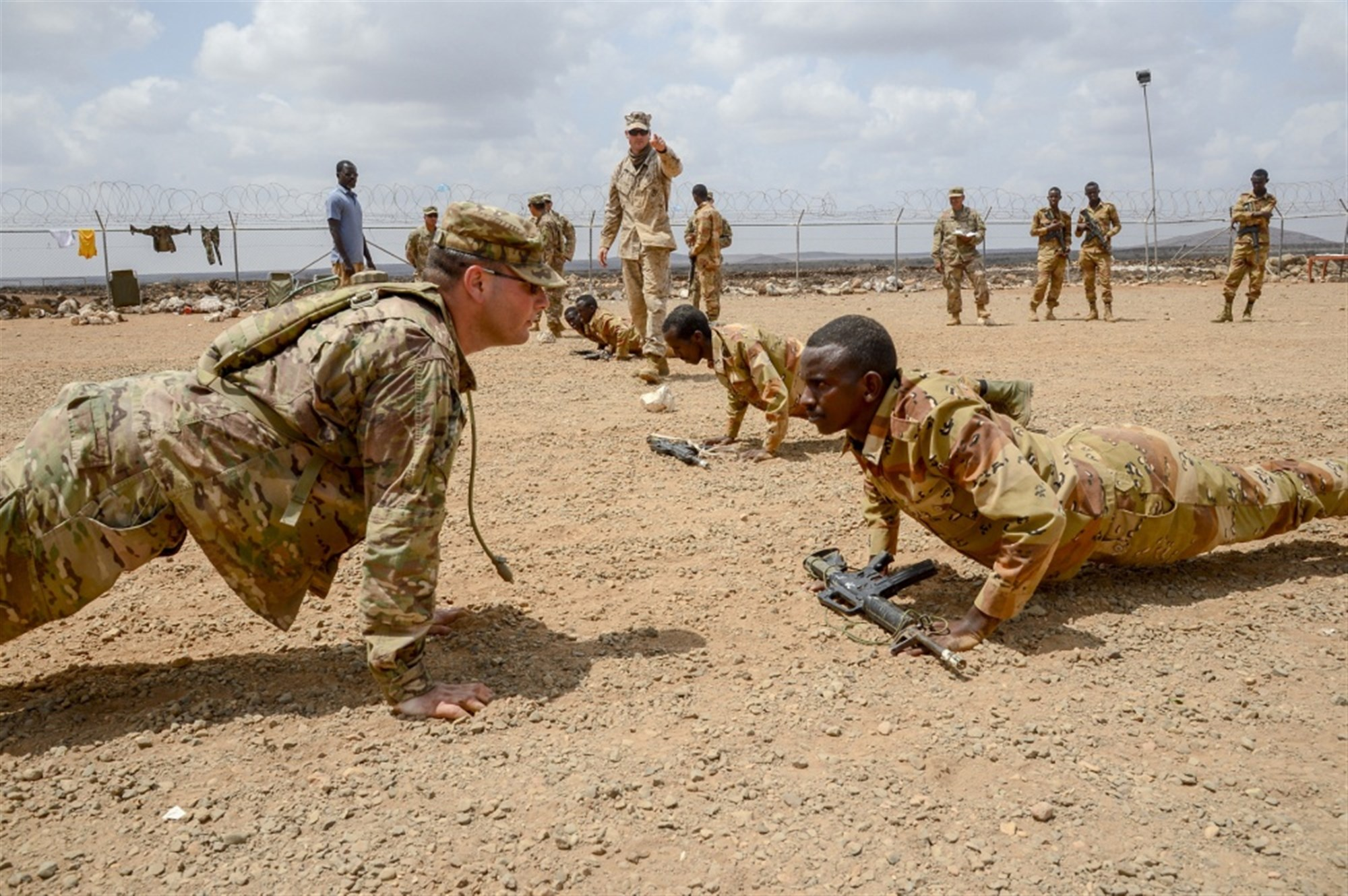 U.S. Army Sergeant Vincent Merriman, Alpha Company, 3rd Battalion, 141st Infantry Regiment, Texas National Guard, demonstrates a proper pushup for a Djiboutian soldier at a training site outside Djibouti City, April 19, 2018. U.S. service members have been training the Djiboutian Army's Rapid Intervention Battalion, a newly formed crisis response unit.