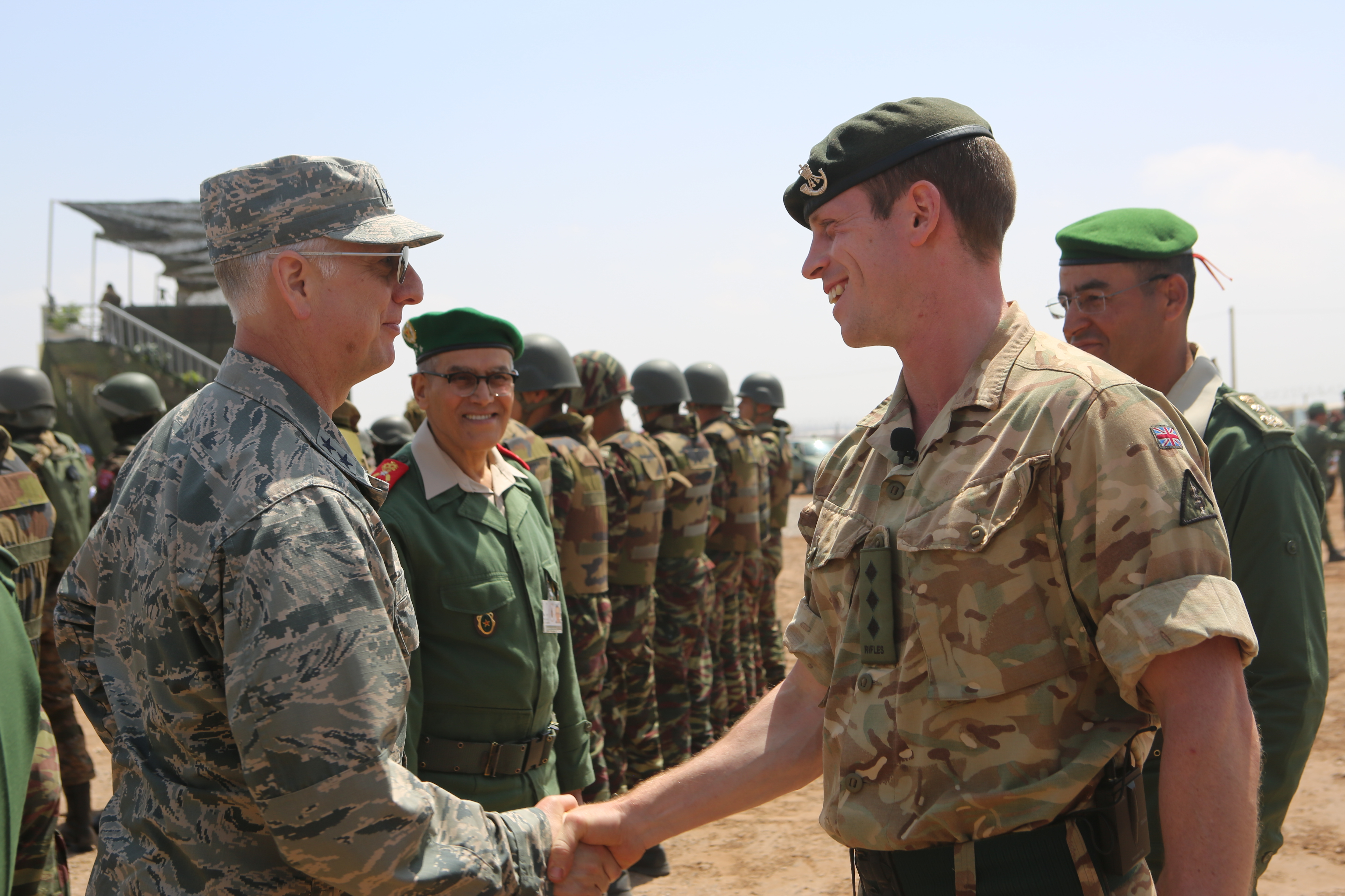 Air Force Maj.Gen. Mark Camerer, director of logistics for U.S. Africa Command, and other distinguished guests shakes hands with British Col. Dom Watson, British 4th Rifles commander, during Exercise African Lion 2018 distinguished visitor tour in Tifnit, Morocco, April 26, 2018. Marines, British soldiers and members of the Moroccan Royal Armed Forces demonstrated tactics, techniques, and procedures from the past two weeks of field training exercises. Exercise African Lion is a continuation of the U.S. and Morocco's long-standing relationship focused on security cooperation. (U.S. Marine Corps photo by Sgt. Averi Coppa/Released)
