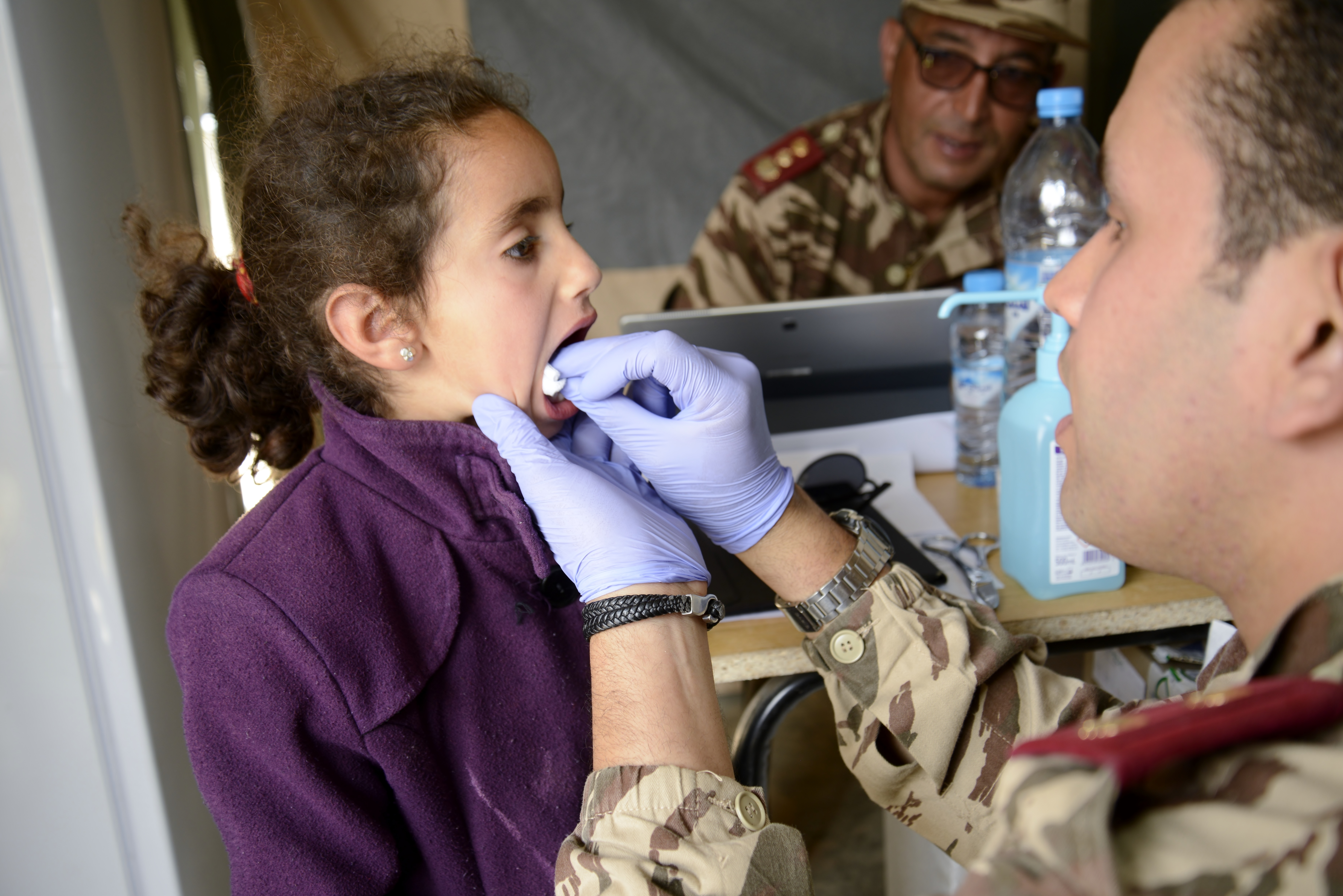 Moroccan 1stLt. Hamza Layat, a pharmacist and member of the Moroccan Royal Armed Forces, provides aid to a girl after a having a dental procedure during the Humanitarian Civic Assistance component of Exercise African Lion 2018 in Bounaamane, Morocco, April 25, 2018.  Exercise African Lion 2018 is a Chairman of the Joint Chiefs of Staff-sponsored, U.S. African Command-scheduled, U.S. Marine Corps Forces Europe and Africa-led, joint and combined exercise conducted in the Kingdom of Morocco. African Lion offers an opportunity to improve interoperability and cooperation while demonstrating the strong military bond that exists between the participating nations. (U.S. Army National Guard photo by Maj. Samantha Madsen)
