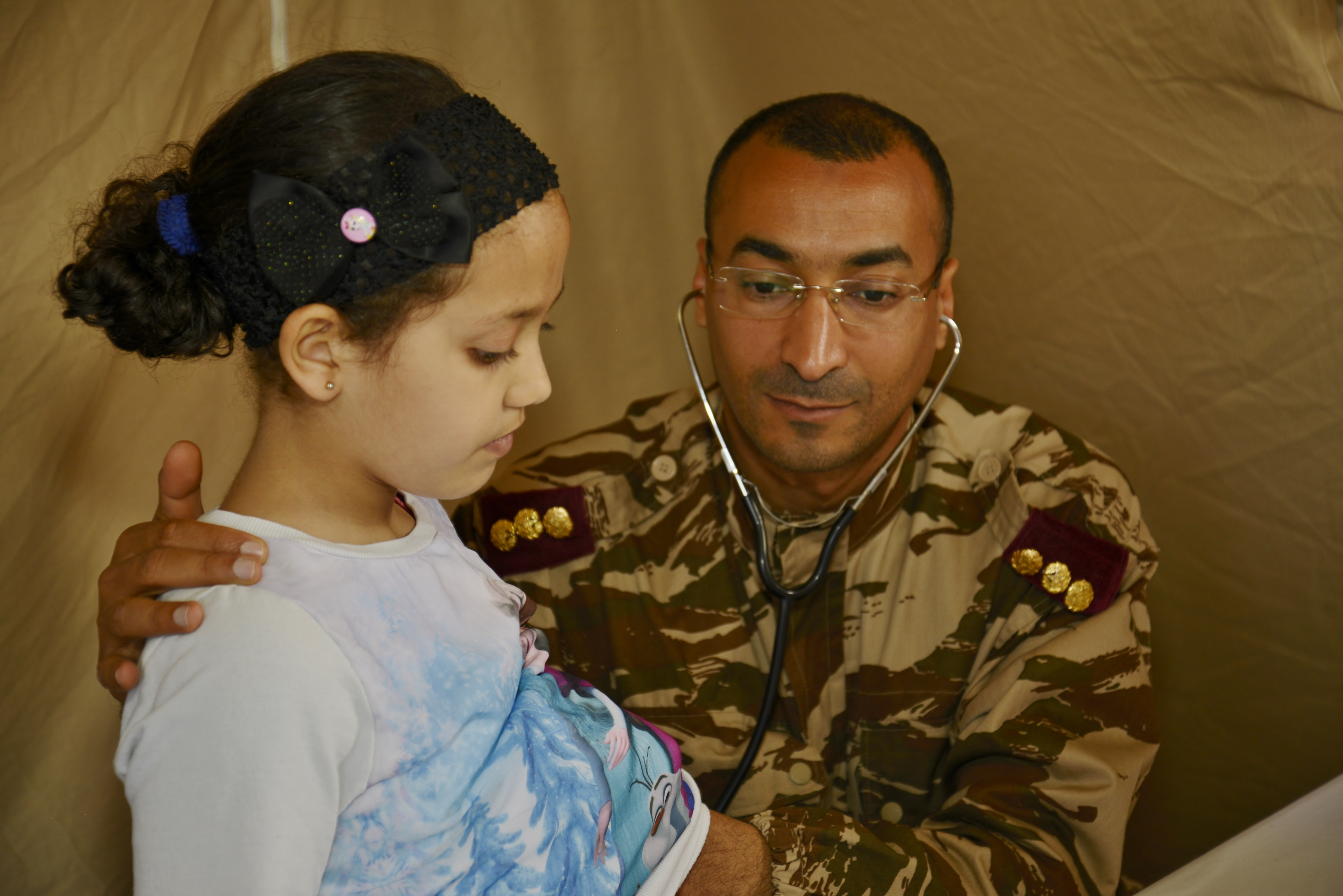 Moroccan Capt. Abdelilah Radi, a pediatrician with the Moroccan Royal Armed Forces, checks the heart of a girl during the Humanitarian Civic Assistance component of Exercise African Lion 2018 in Bounaamane, Morocco, April 24, 2018.  Exercise African Lion 2018 is a Chairman of the Joint Chiefs of Staff-sponsored, U.S. African Command-scheduled, U.S. Marine Corps Forces Europe and Africa-led, joint and combined exercise conducted in the Kingdom of Morocco. African Lion offers an opportunity to improve interoperability and cooperation while demonstrating the strong military bond that exists between the participating nations. (U.S. Army National Guard photo by Maj. Samantha Madsen)