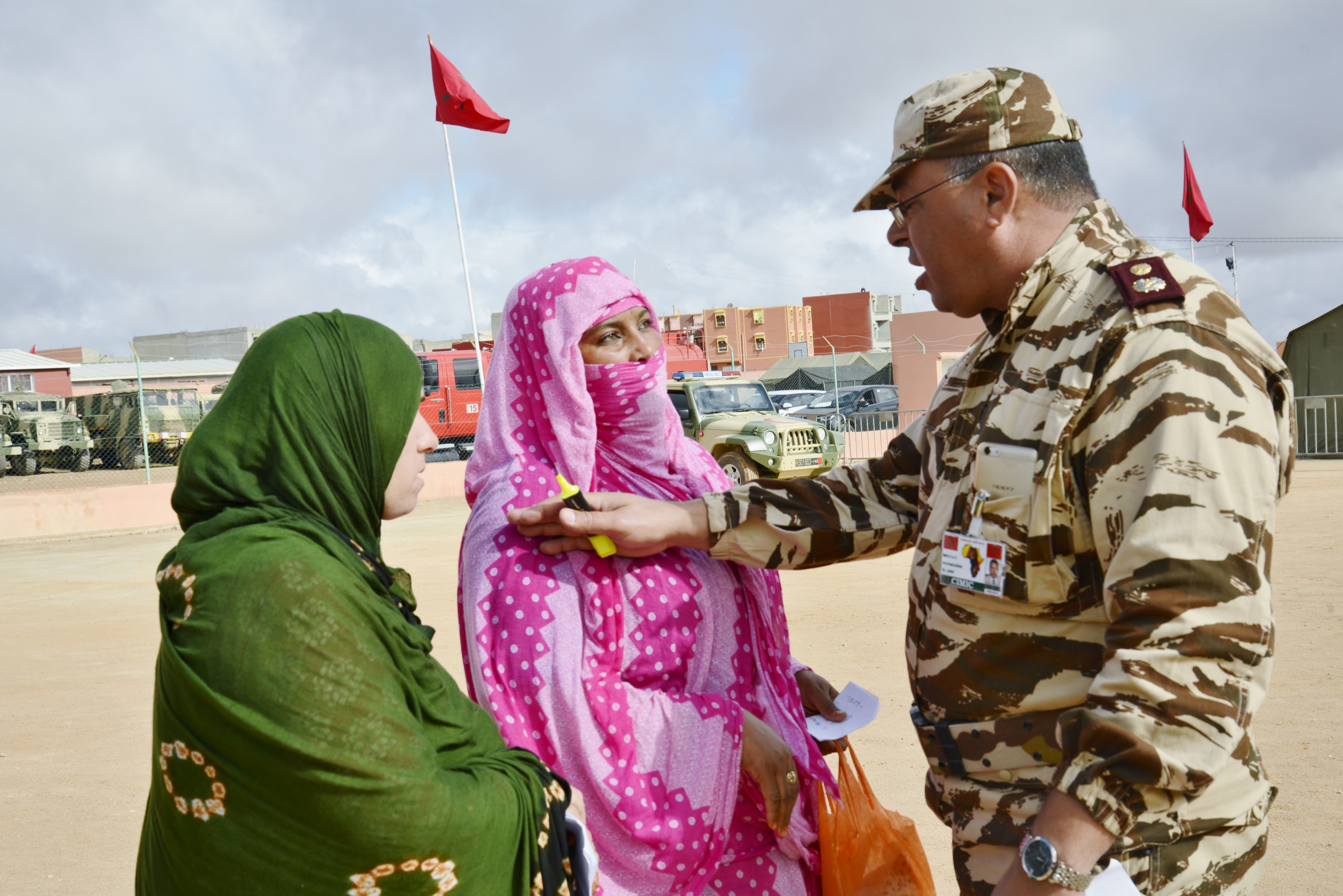 A member of Moroccan Royal Armed Forces assists two women during the Humanitarian Civic Assistance component of Exercise African Lion 2018 in Bounaamane, Morocco, April 24, 2018.  Exercise African Lion 2018 is a Chairman of the Joint Chiefs of Staff-sponsored, U.S. African Command-scheduled, U.S. Marine Corps Forces Europe and Africa-led, joint and combined exercise conducted in the Kingdom of Morocco. African Lion offers an opportunity to improve interoperability and cooperation while demonstrating the strong military bond that exists between the participating nations. (U.S. Army National Guard photo by Maj. Samantha Madsen)