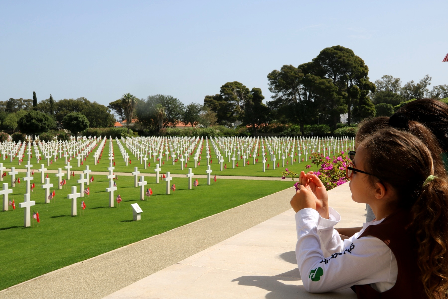 Members of a local Girl Scout troop look out across the graves of American servicemen who are laid to rest at the North Africa American Cemetery and Memorial, just prior to the Memorial Day ceremony in Carthage, Tunisia, May 28, 2018. (Photo by Zouhaier SFAXI, U.S. Embassy Tunis)