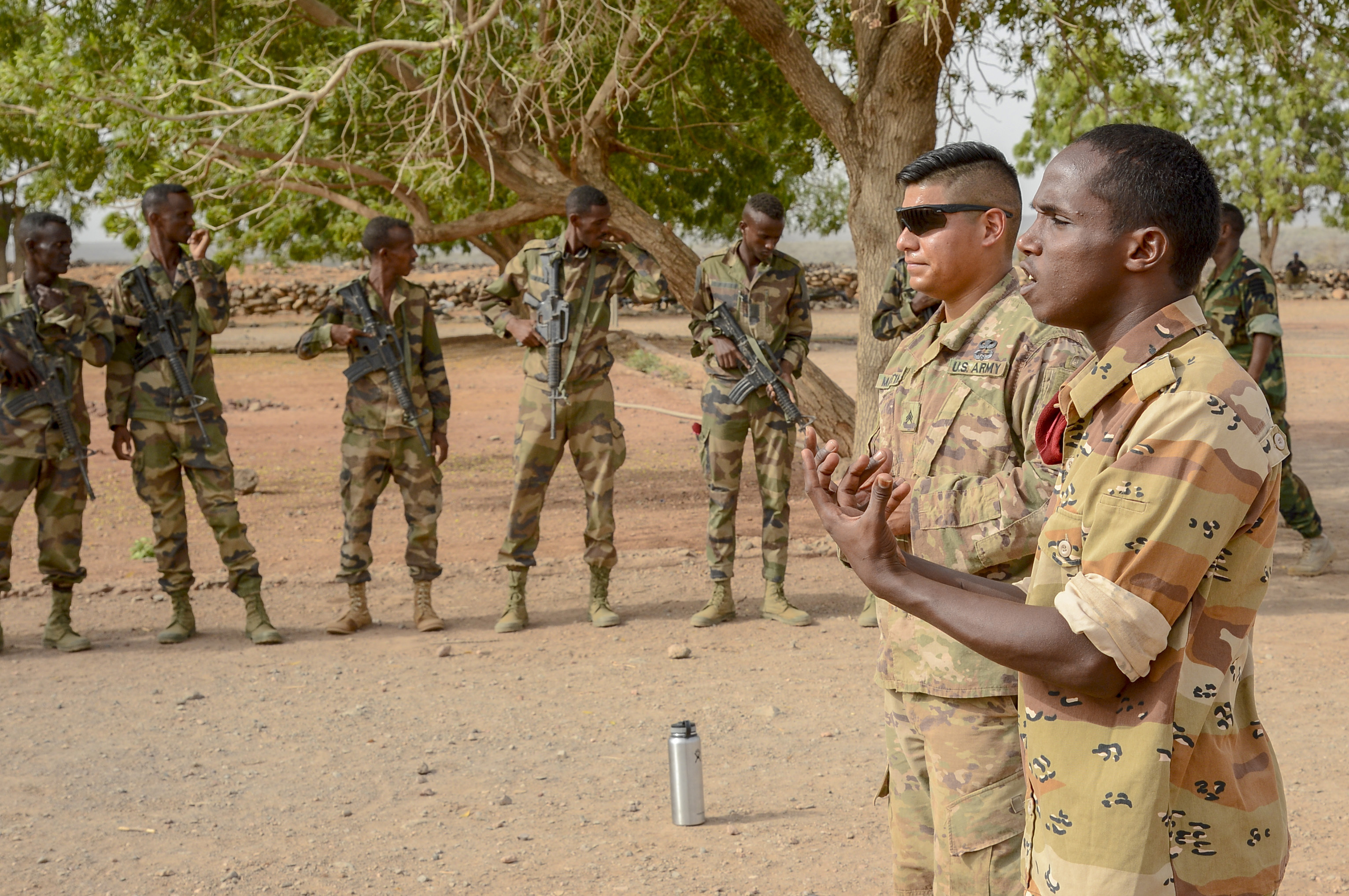 A non-commissioned officer with the Djiboutian Army's Rapid Intervention Battalion (RIB) and U.S. Army Sergeant Daniel Martinez, Bravo Co., 1st Battalion, 141st Infantry Regiment, Texas National Guard, instruct new recruits at a training site outside Djibouti City, July 3, 2018. The RIB is a U.S. Army trained unit that was formed to respond to crises and promote regional security and stability in East Africa. (U.S. Navy Photo by Mass Communication Specialist 2nd Class Timothy M. Ahearn)
