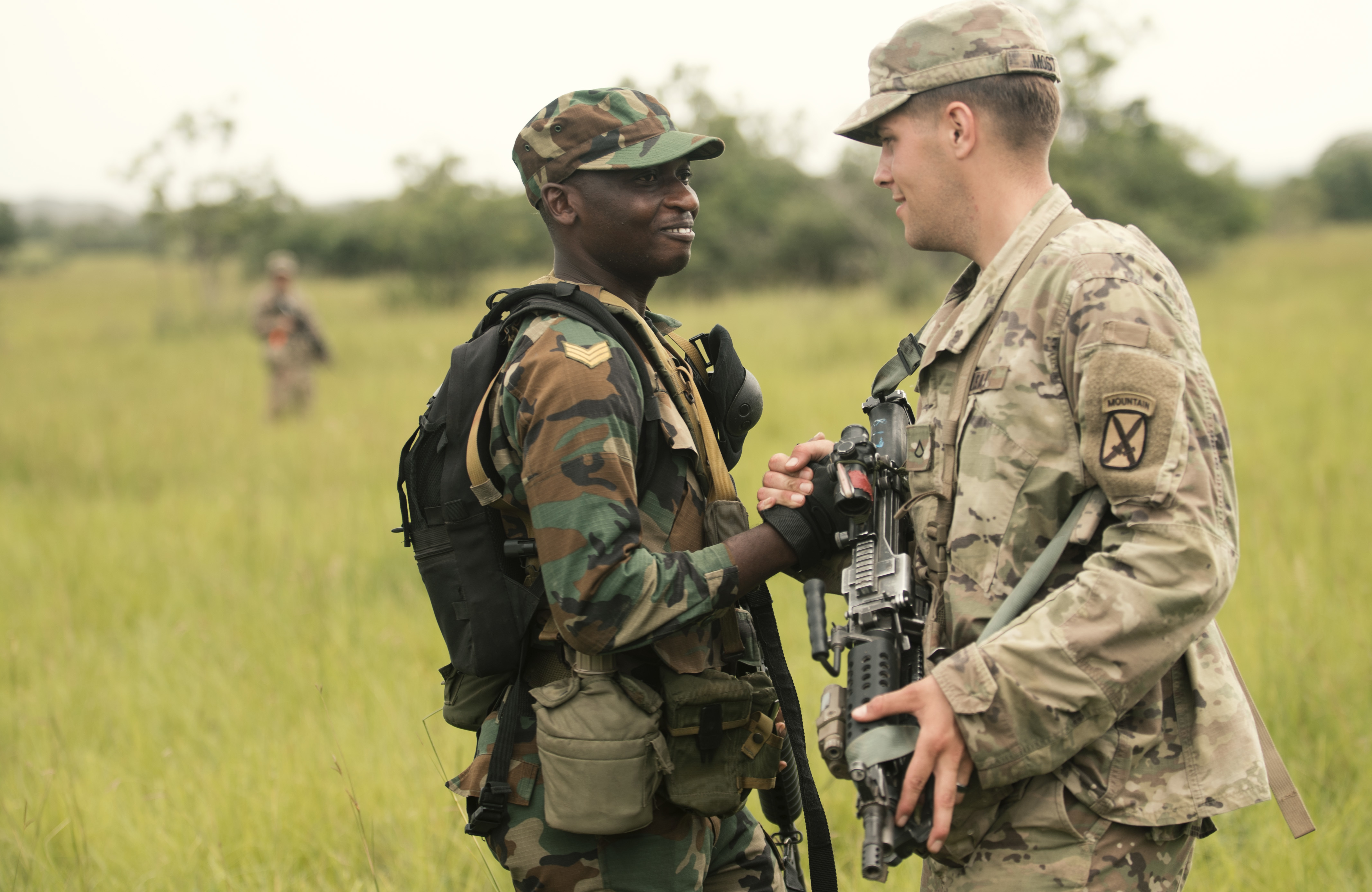 A soldier with the Ghana Armed Forces and a Soldier with U.S. Army's 1-32 Infantry Regiment, 1st Brigade Combat Team, 10th Mountain Division greet each other during a field training exercise as part of United Accord 2018 at the Bundase Training Camp, Ghana July 16, 2018. United Accord 2018 is a Ghana Armed Forces & U.S. Army Africa hosted exercise consisting of four combined, joint components: a computer-programmed exercise (CPX), field training exercise (FTX), Jungle Warfare School (JWS) and medical readiness training exercise (MEDRETE) (U.S. Navy Photo by MC2 Douglas Parker)