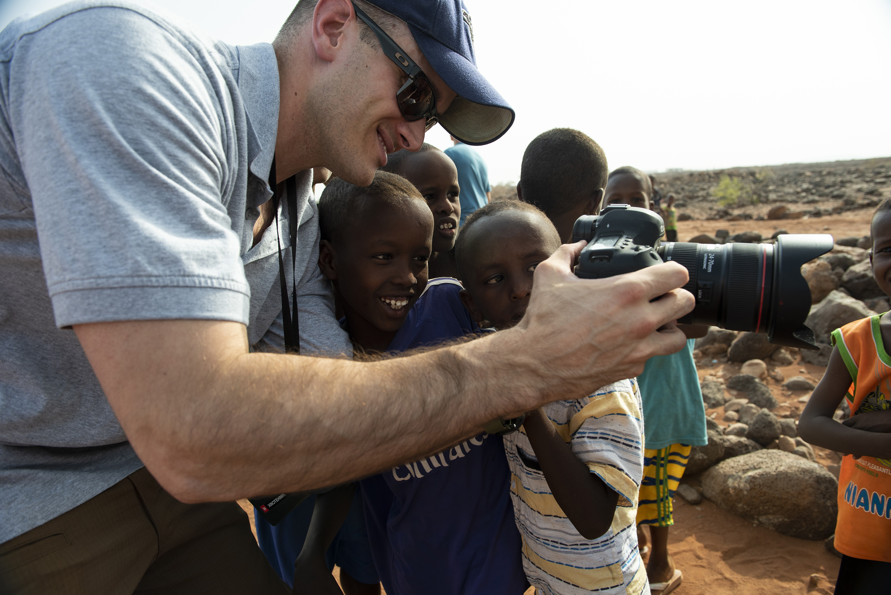 U.S. Air Force Master Sgt. Andrew Sinclair, broadcaster, Combined Joint Task Force - Horn of Africa, public affairs, demonstrates how to use his camera to Djiboutian children, outside of Chebelley Village, Djibouti, Aug. 3, 2018. Sinclair was there to document a soccer game in which U.S. Service members teamed up with children from the nearby village as part of a community engagement event organized by the 404th Civil Affairs Battalion. (U.S. Air National Guard photo by Master Sgt. Sarah Mattison)