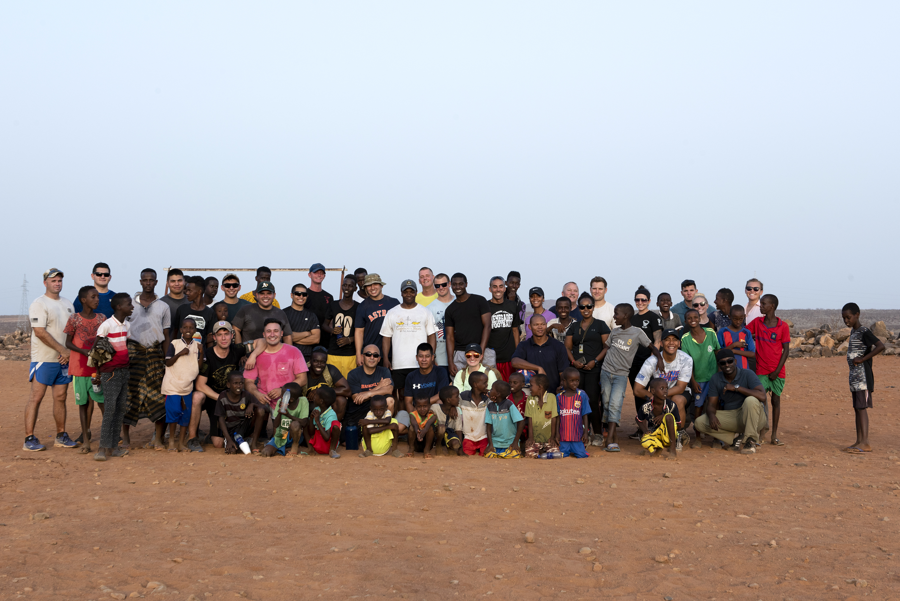 U.S. Service members assigned to Combined Joint Task Force - Horn of Africa pose for a group photo with children from the nearby village outside of Chebelley Village, Djibouti, Aug. 3, 2018. Over 30 Soldiers and Airmen volunteered for the outreach event organized by the 404th Civil Affairs Battalion. (U.S. Air National Guard photo by Master Sgt. Sarah Mattison)