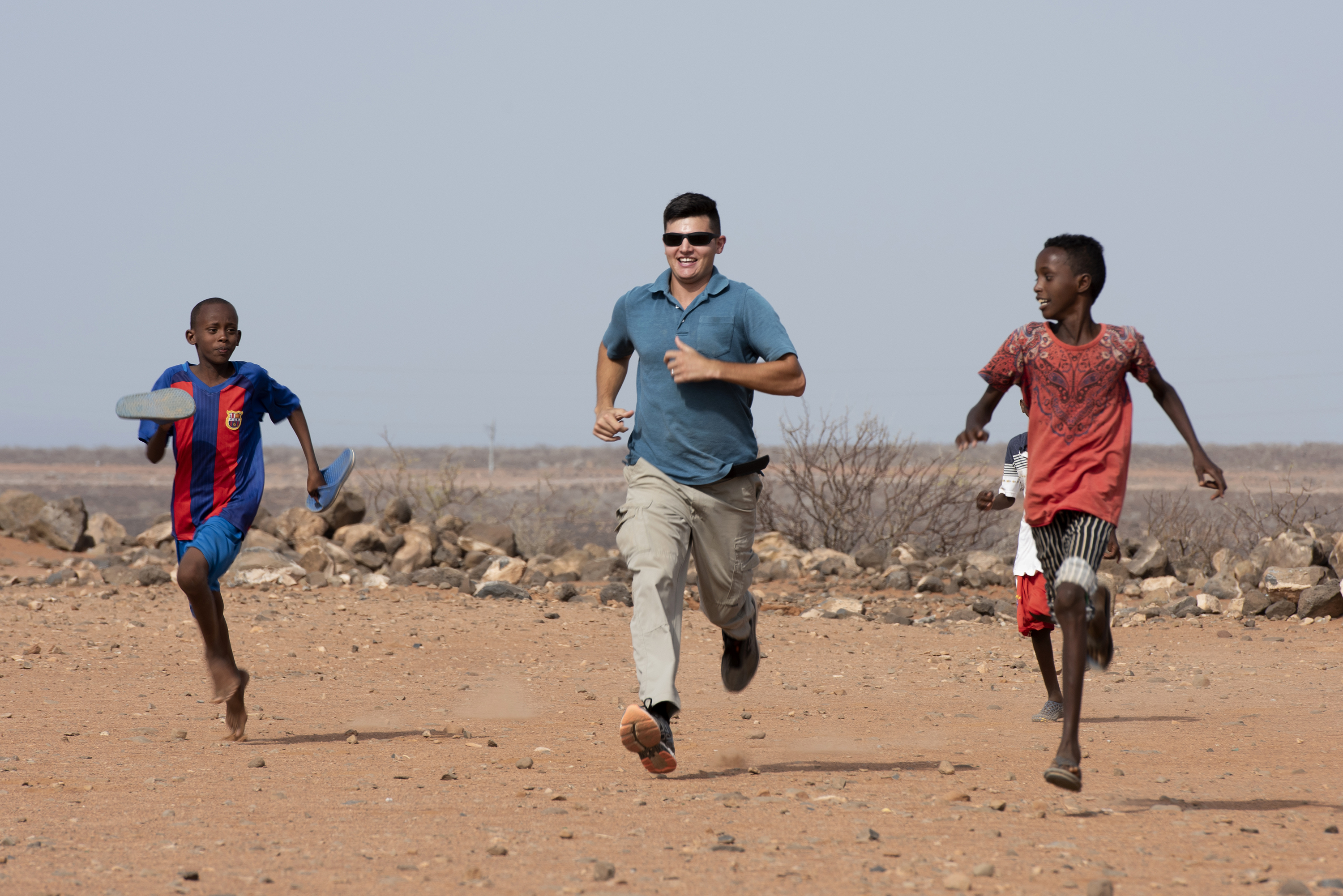 U.S. Army Sgt. Eythan Caputo, a civil affairs specialist with the 404th Civil Affairs Battalion, races with children from the local village outside of Chebelley Village, Djibouti, Aug. 3, 2018. Caputo was one of 30 service members participating in a outreach event organized by the 404th Civil Affairs Battalion. (U.S. Air National Guard photo by Master Sgt. Sarah Mattison)