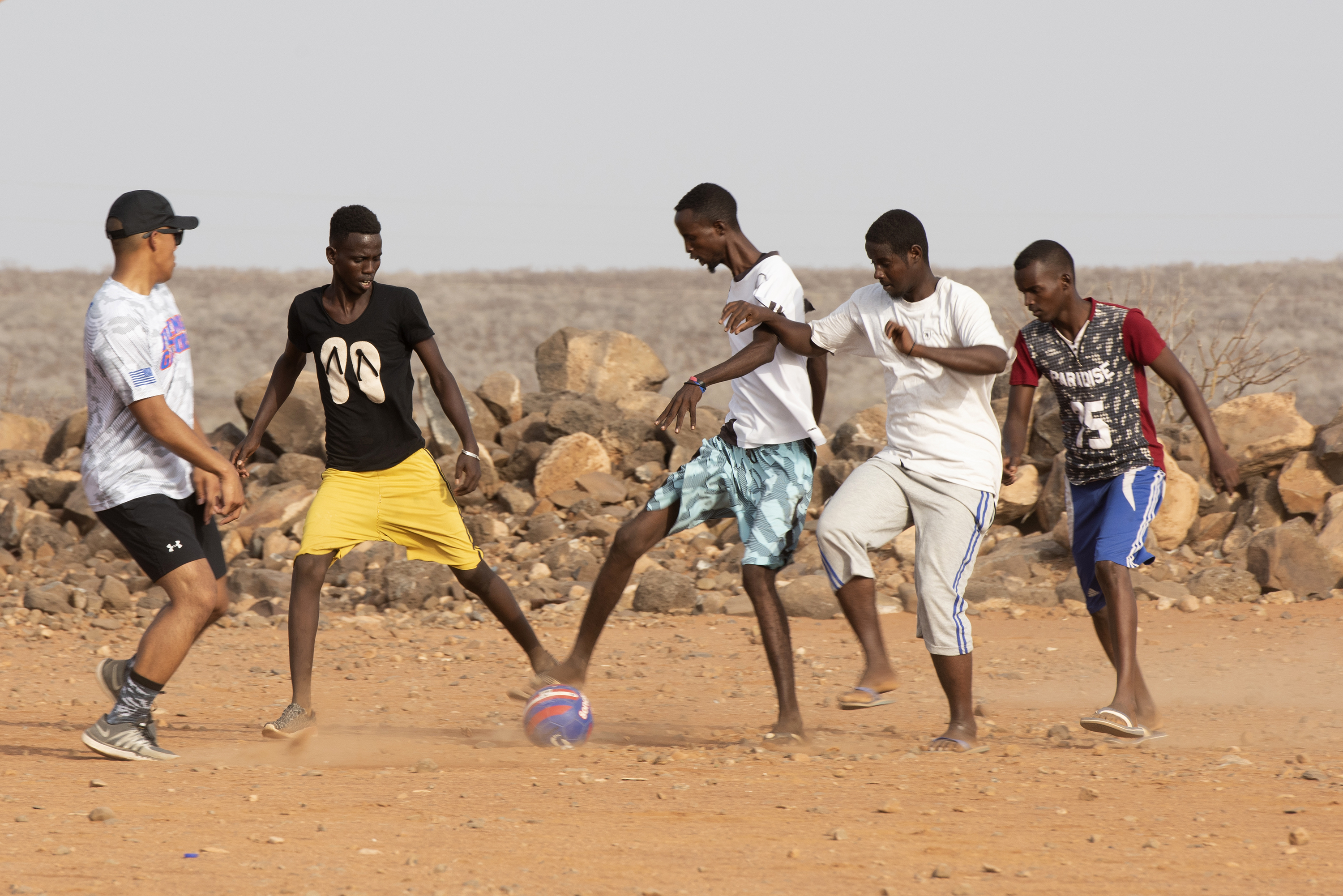 U.S. Air Force 1st Lt. Darren Domingo, left, officer in charge, Combat Camera, assigned to Combined Joint Task Force - Horn of Africa, plays soccer with children from the local village outside of Chebelley Village, Djibouti, Aug. 3, 2018. Domingo was one of approximately 30 service members participating in an outreach event organized by the 404th Civil Affairs Battalion. (U.S. Air National Guard photo by Master Sgt. Sarah Mattison)