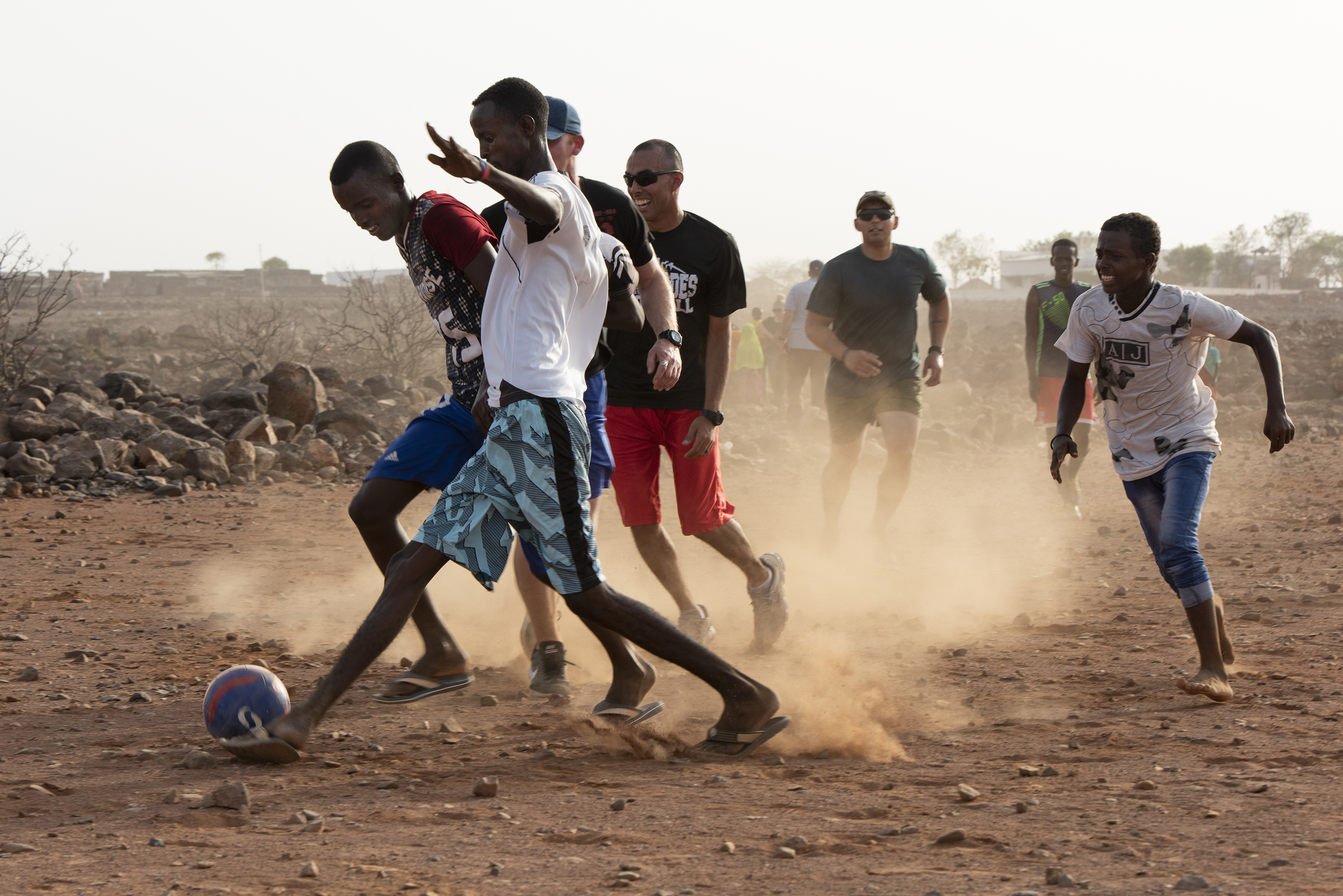 U.S. Service members assigned to Combined Joint Task Force - Horn of Africa, participate in a friendly game of soccer with children from the nearby village, outside of Chebelley village, Djibouti, Aug. 3, 2018. Over 30 Soldiers and Airmen volunteered for the outreach event organized by the 404th Civil Affairs Battalion. (U.S. Air National Guard photo by Master Sgt. Sarah Mattison)