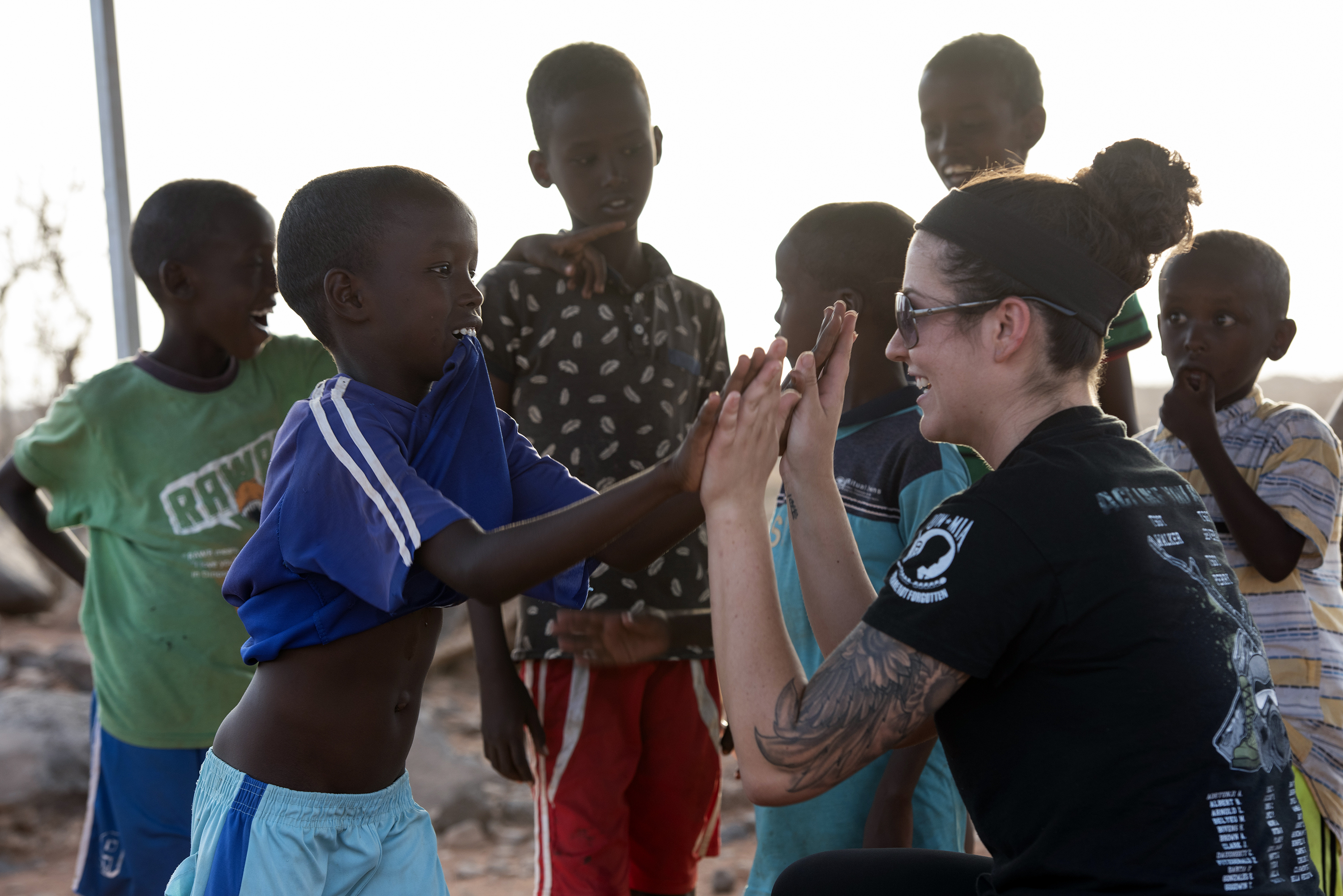 U.S. Air Force Airman 1st Class Taylor Simmons, Services Journeyman, 870th Air Expeditionary Squadron, Combined Joint Task Force - Horn of Africa (CJTF-HOA), interacts with children outside of Chebelley Village, Djibouti, Aug. 3, 2018. Simmons was participating in an outreach event organized by the 404th Civil Affairs Battalion that included 30 service members from CJTF-HOA. (U.S. Air National Guard photo by Master Sgt. Sarah Mattison)