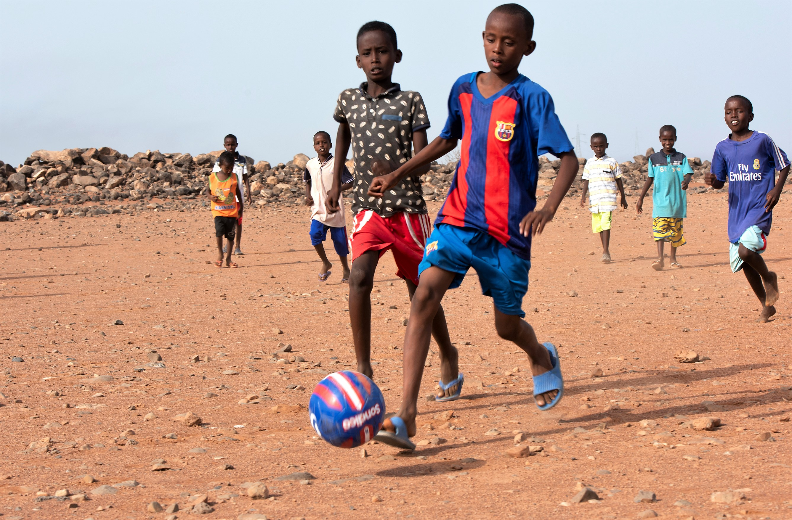 Djiboutian children from Chebelley Village play soccer outside of Chebelley Village, Djibouti, Aug. 3, 2018. The 404th Civil Affairs Battalion organized an outreach event that included 30 service members from Combined Joint Task Force - Horn of Africa. (U.S. Air National Guard photo by Master Sgt. Sarah Mattison)